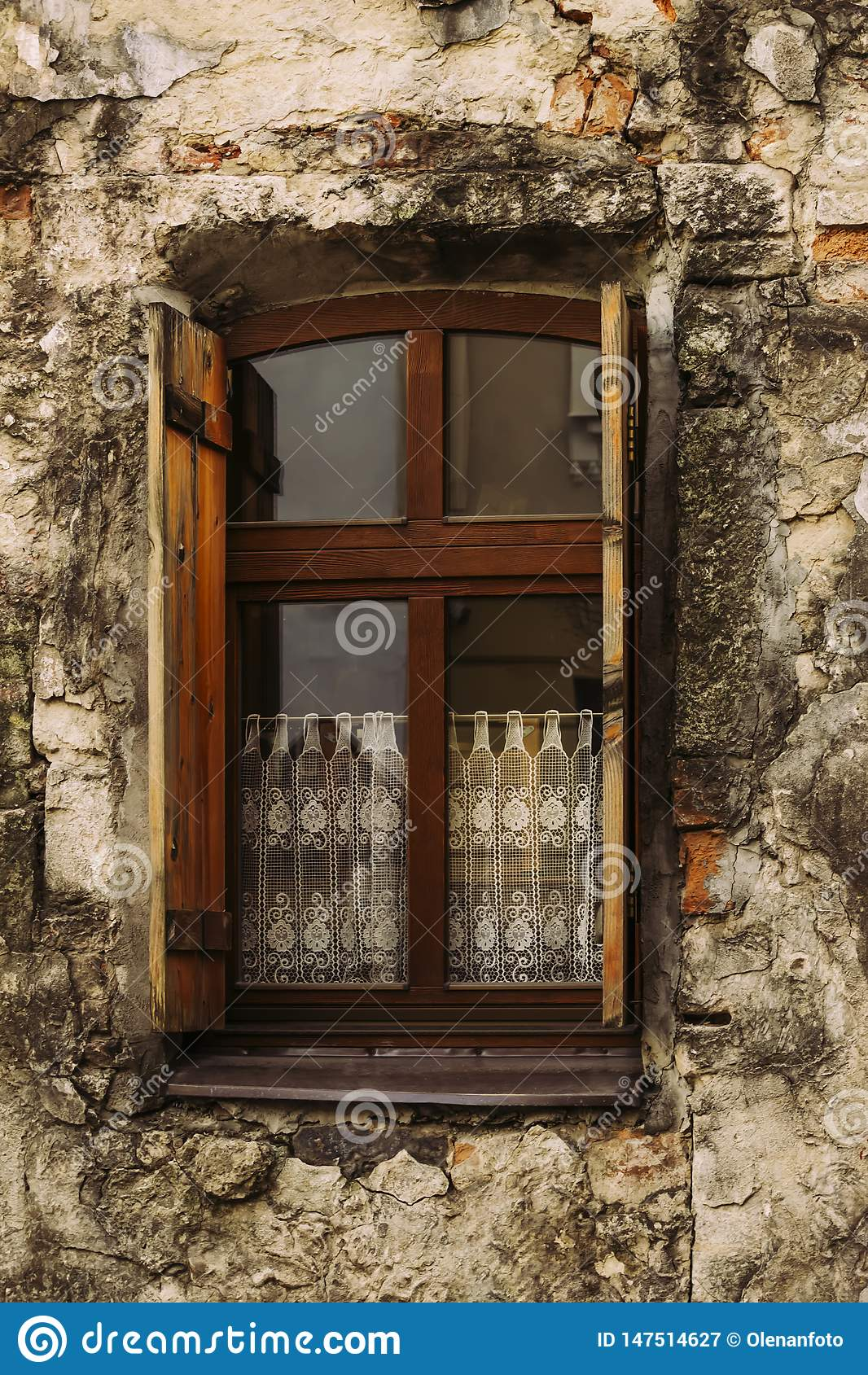 Une vieille fenêtre avec les volets ouverts dans une vieille maison