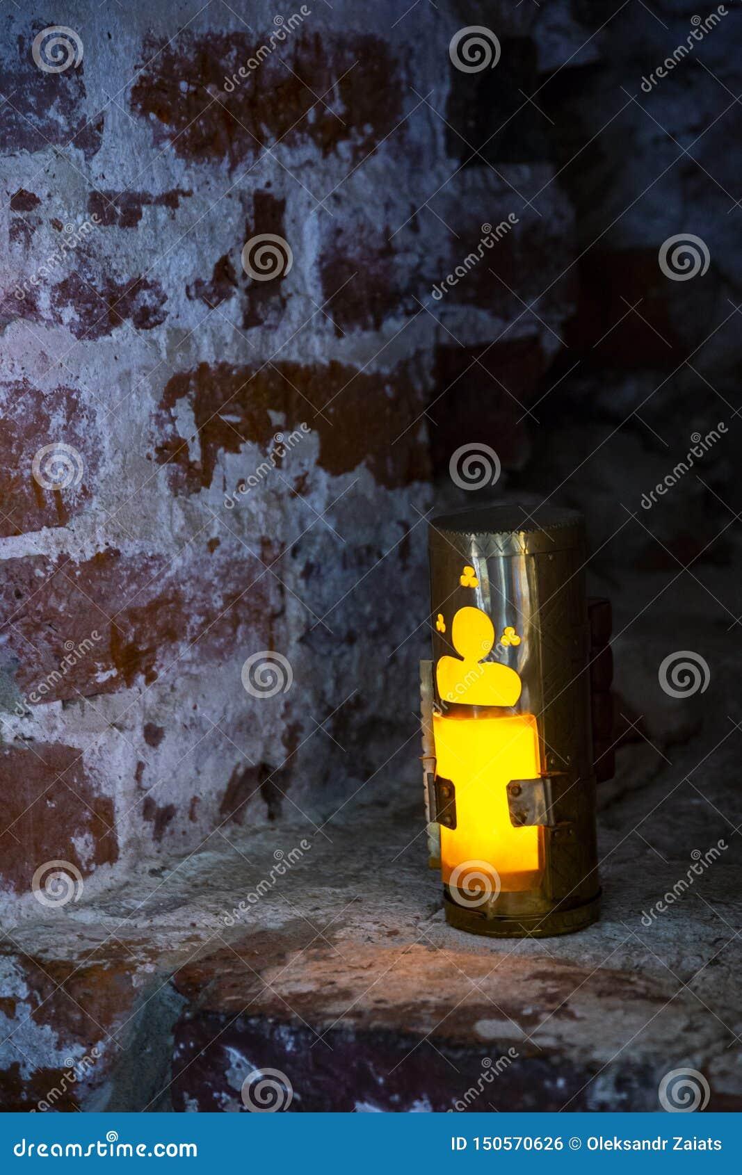 Une vieille lampe de bougie dans le créneau sur le mur de briques La lanterne antique de bougie illumine du créneau