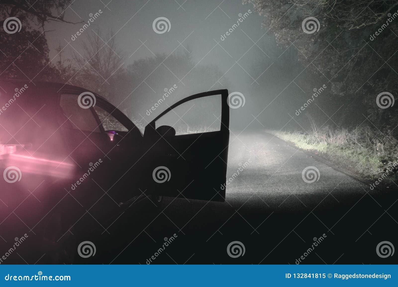 Une voiture avec elle est allumée les phares et la porte ouverte sur les WI brumeux fantasmagoriques