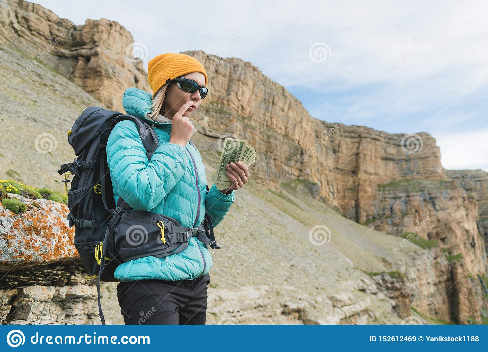 Une voyageuse de fille dans des lunettes de soleil et avec un sac à dos sur le fond des roches de haute montagne tient pensivemen