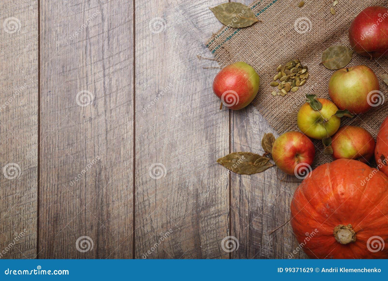 Une vue supérieure des deux potirons lumineux lumineux et des pommes colorées sur un tissu rustique sur un fond en bois Copiez l