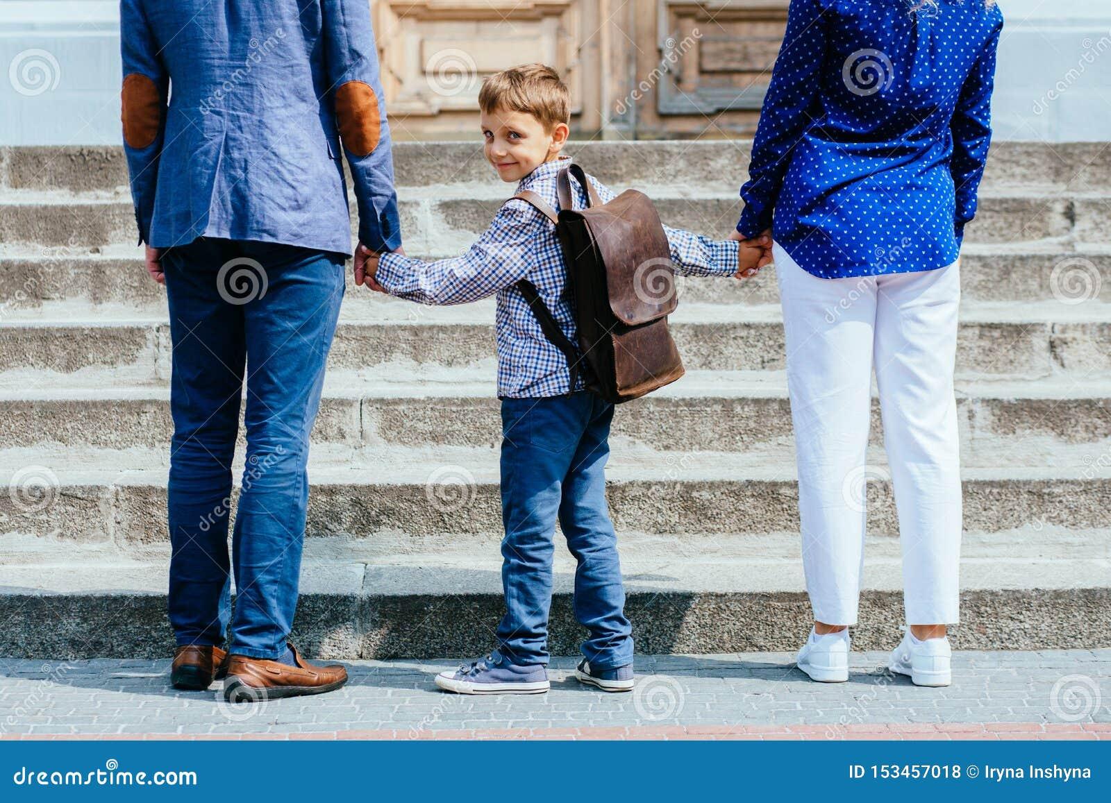 Unerkennbare Eltern nehmen Kind zur Schule Schüler der Grundschule gehen Studie mit Rucksack Hintere Ansicht des Vaters, Mutter