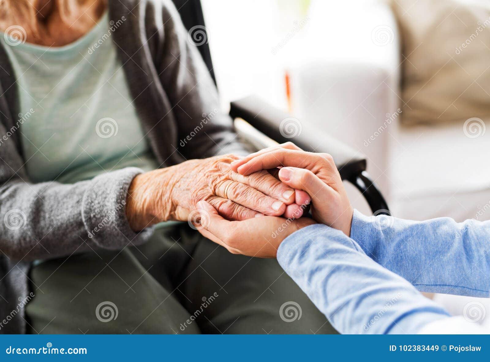 Unerkennbarer Gesundheitsbesucher und eine ältere Frau während der Hauptkraft