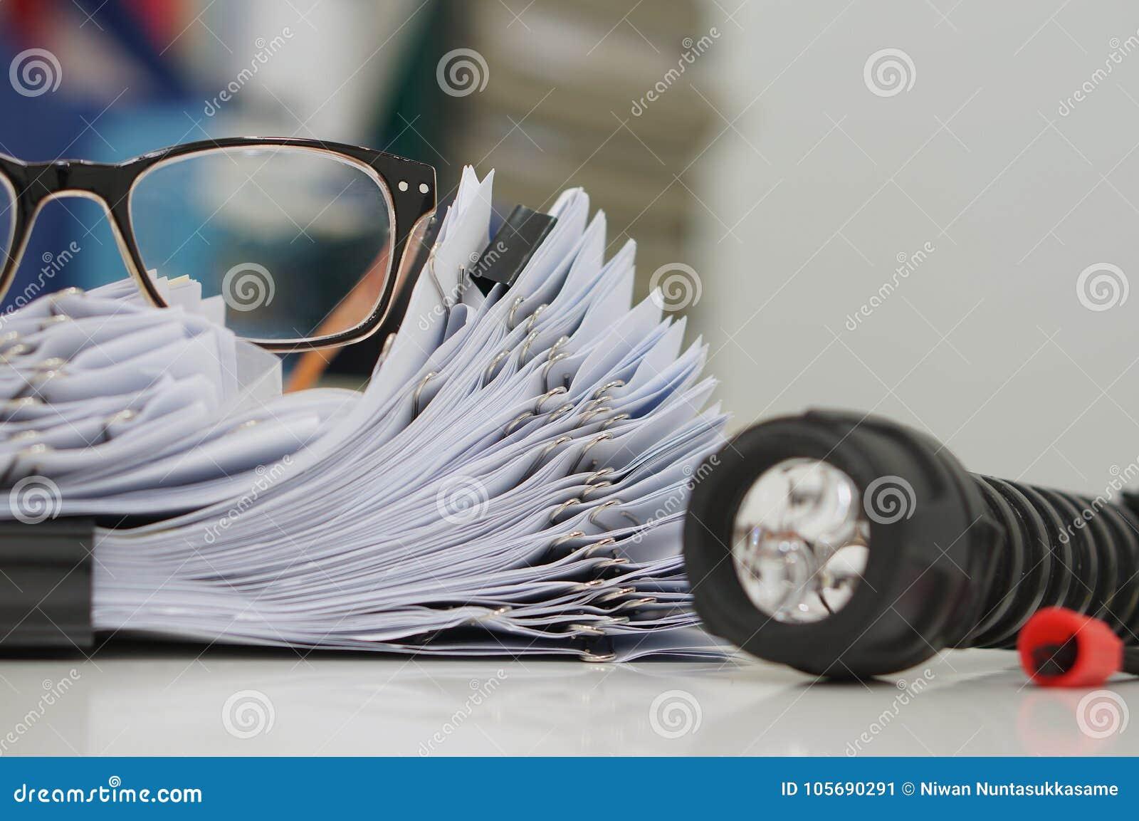 Unfertiges Dokument, Stapel Papierarchive mit Clipn auf Schreibtisch für Bericht, Gläser und Taschenlampe