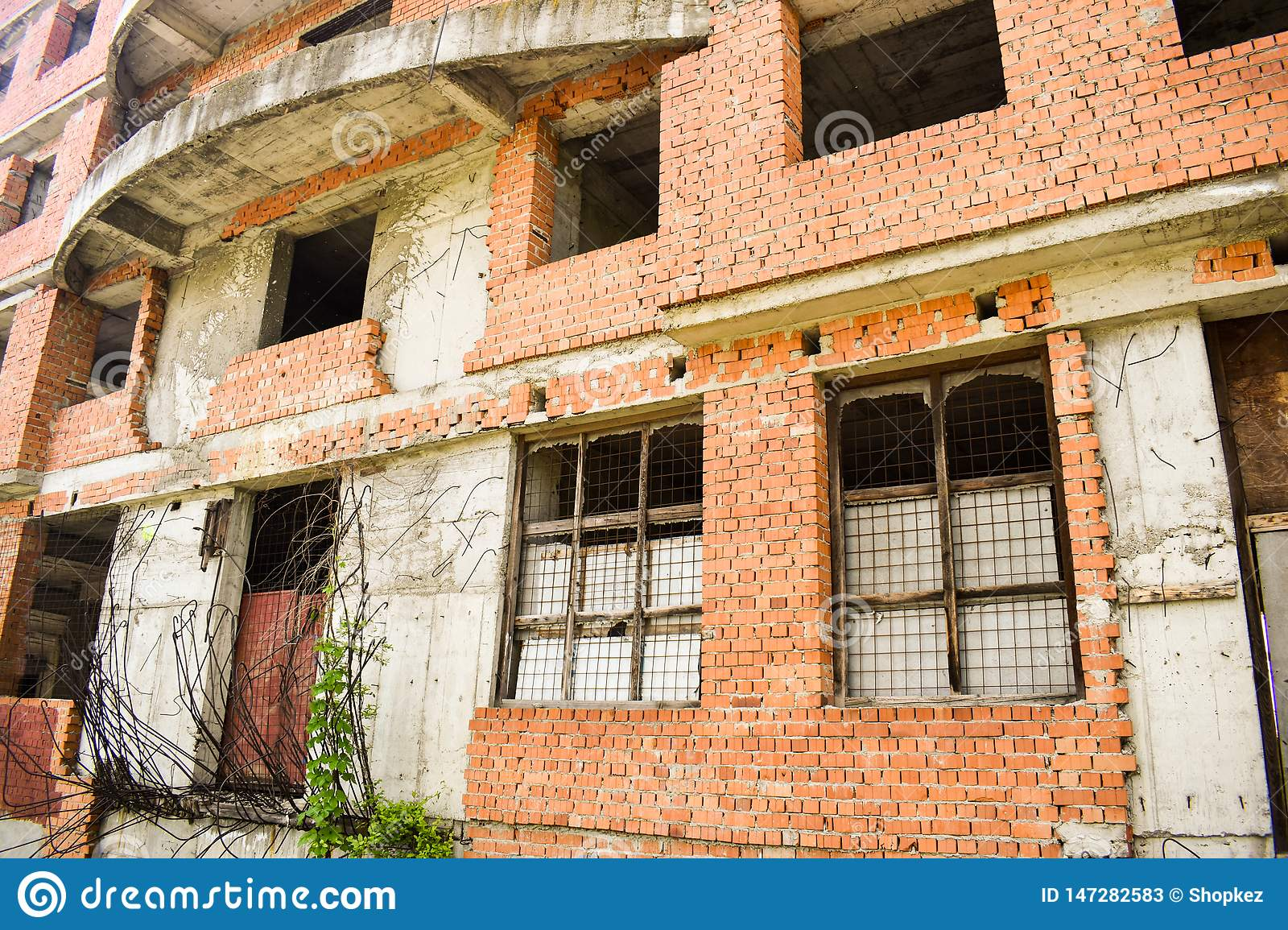 Unfinished building in the downtown. Abandoned building project with red bricks and wild vegetation