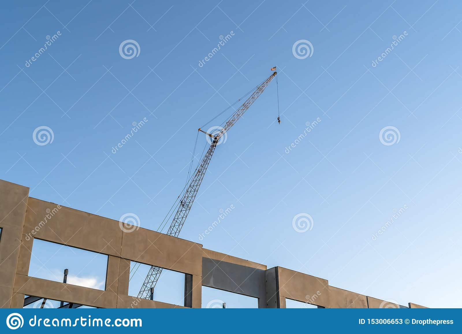 Unfinished building exterior and construction crane with blue sky background