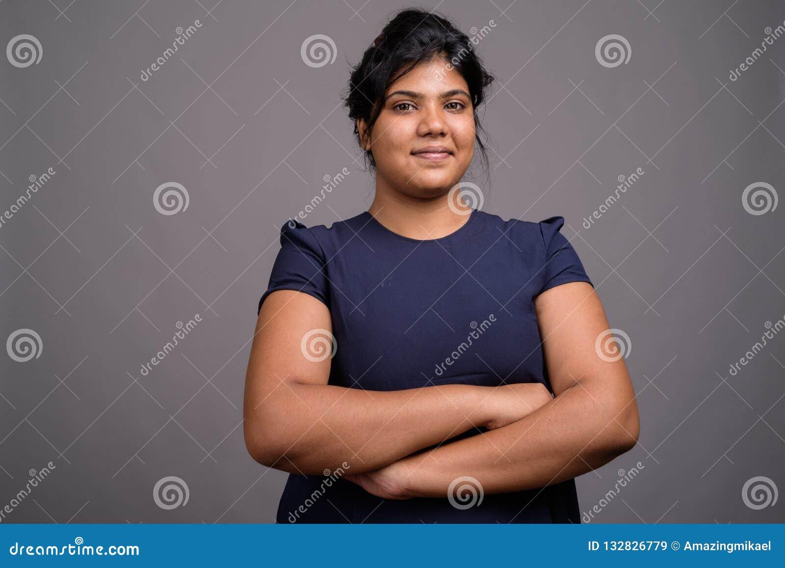 Ung överviktig härlig indisk kvinna mot grå bakgrund