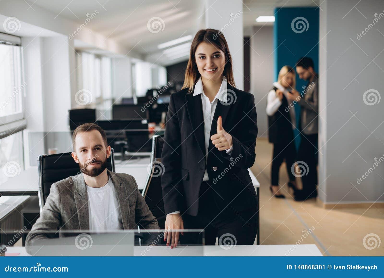 Ung affärskvinna och affärsman som tillsammans i regeringsställning arbetar Härlig tumme för visning för kontorsflicka upp