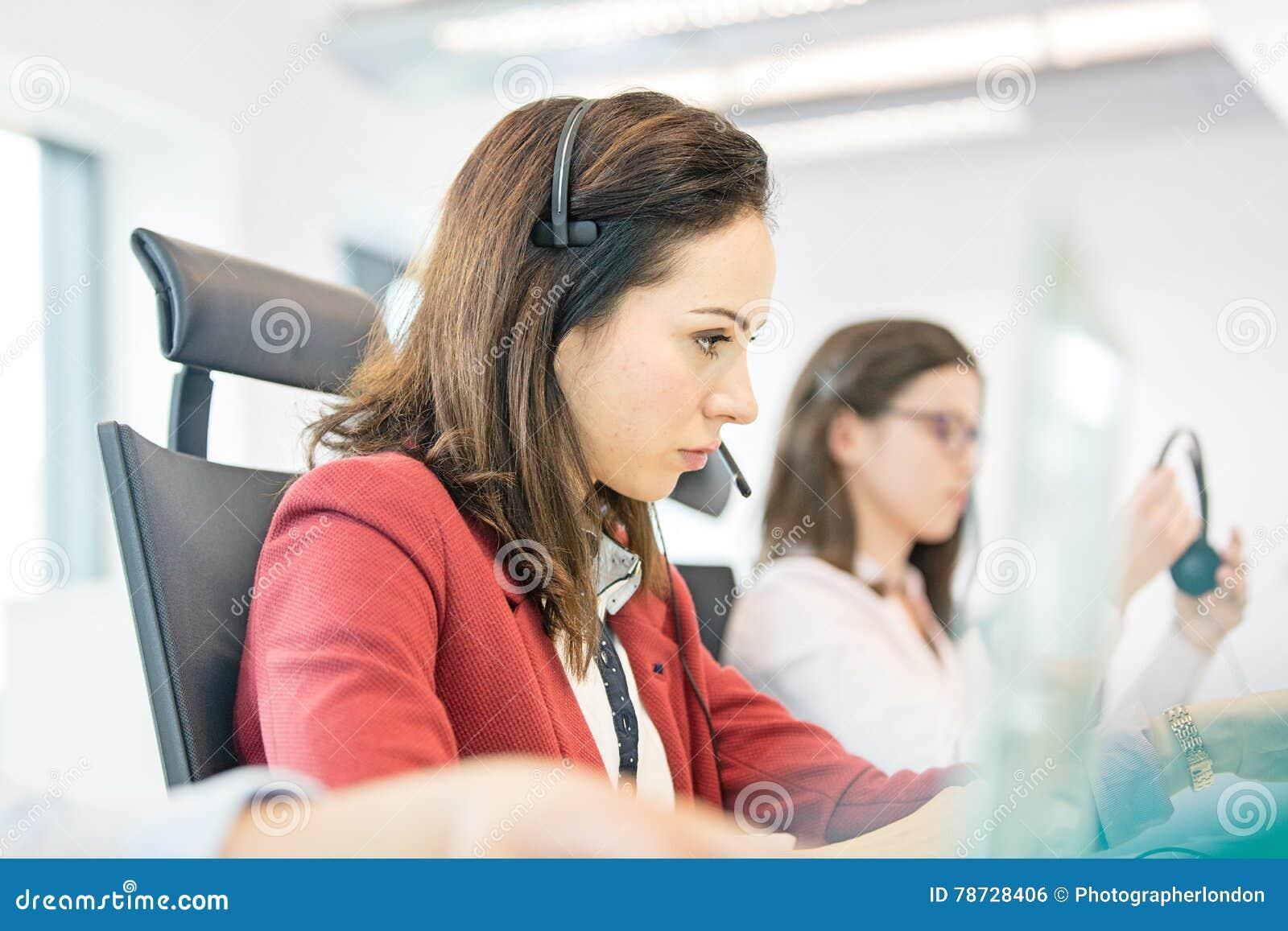 Ung affärskvinna som använder hörlurar med mikrofon med den kvinnliga kollegan i bakgrund på kontoret