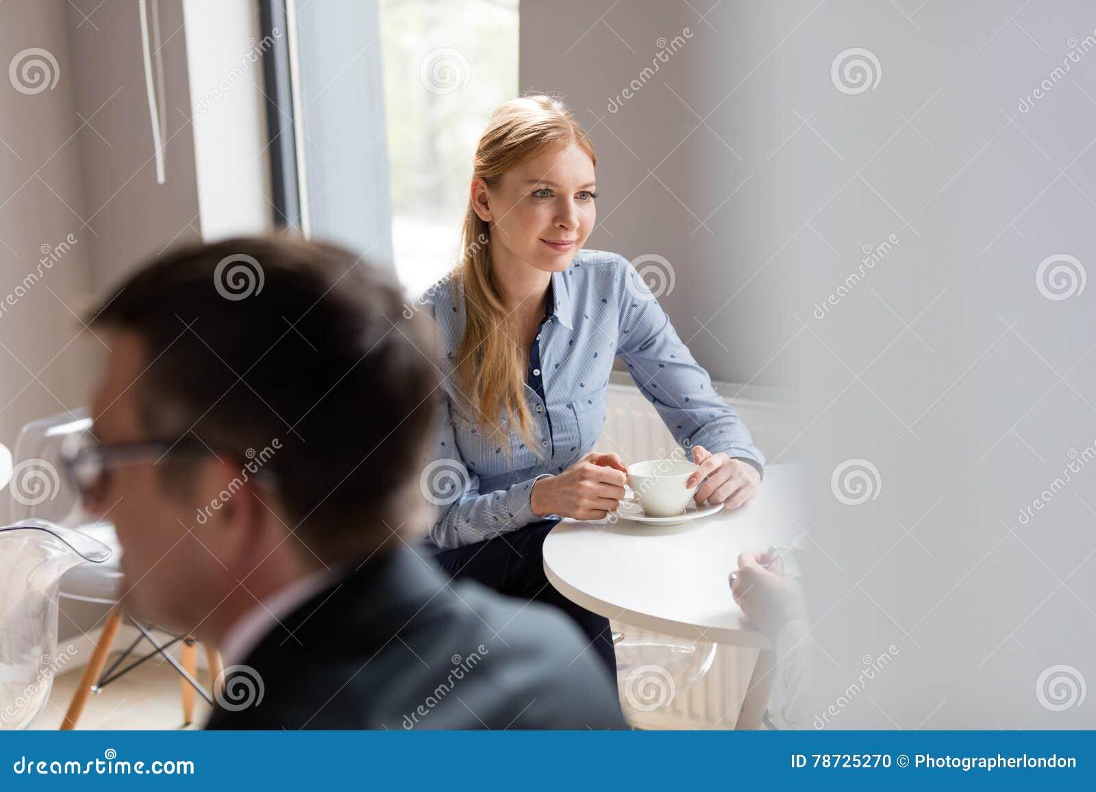 Ung affärskvinna som har kafeterian för kaffe i regeringsställning