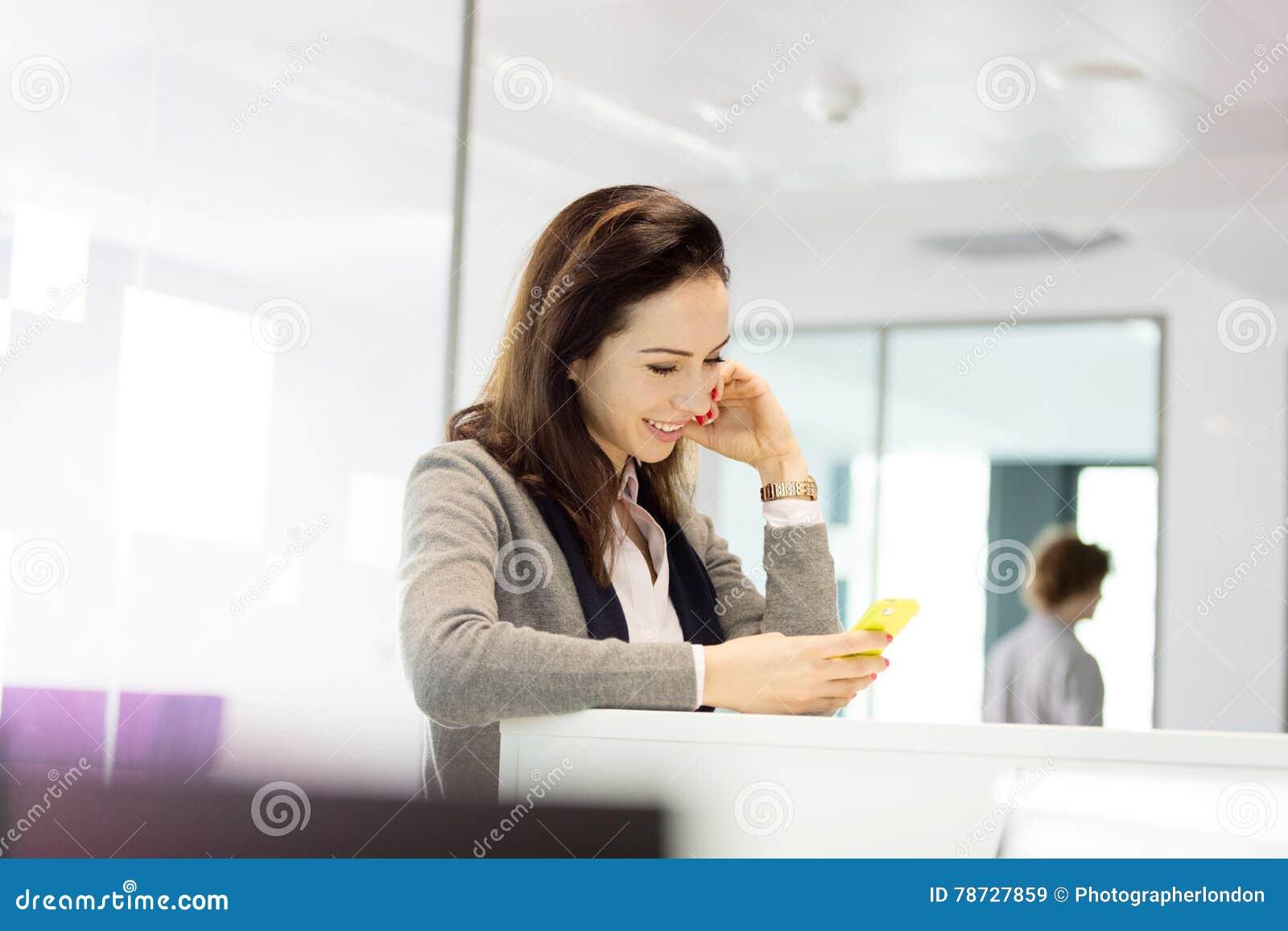 Ung affärskvinna som i regeringsställning använder mobiltelefonen