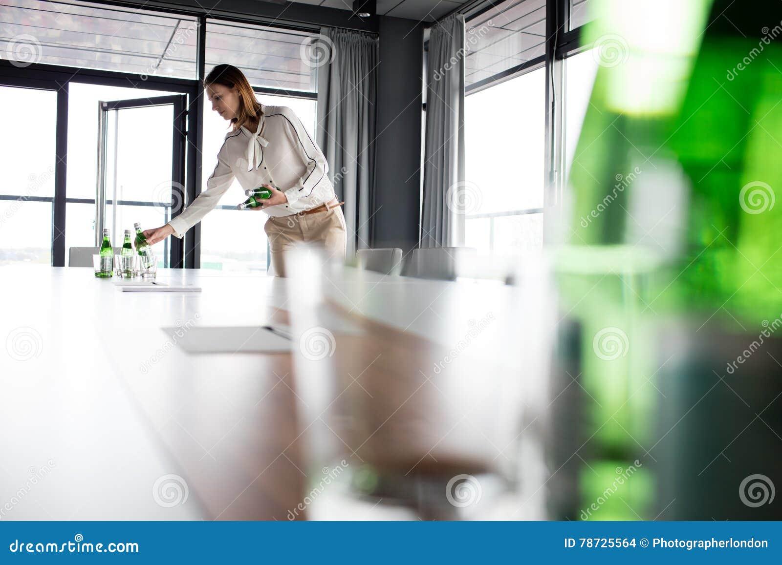 Ung affärskvinna som i regeringsställning förlägger vattenflaskor på konferenstabellen
