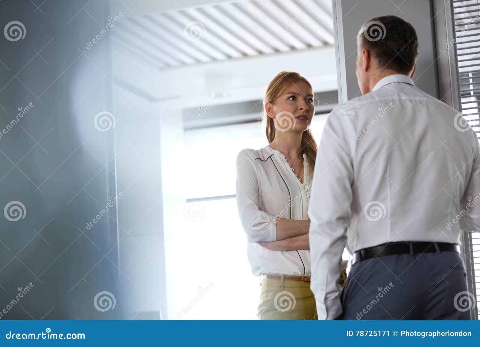Ung affärskvinna som i regeringsställning talar med den manliga kollegan