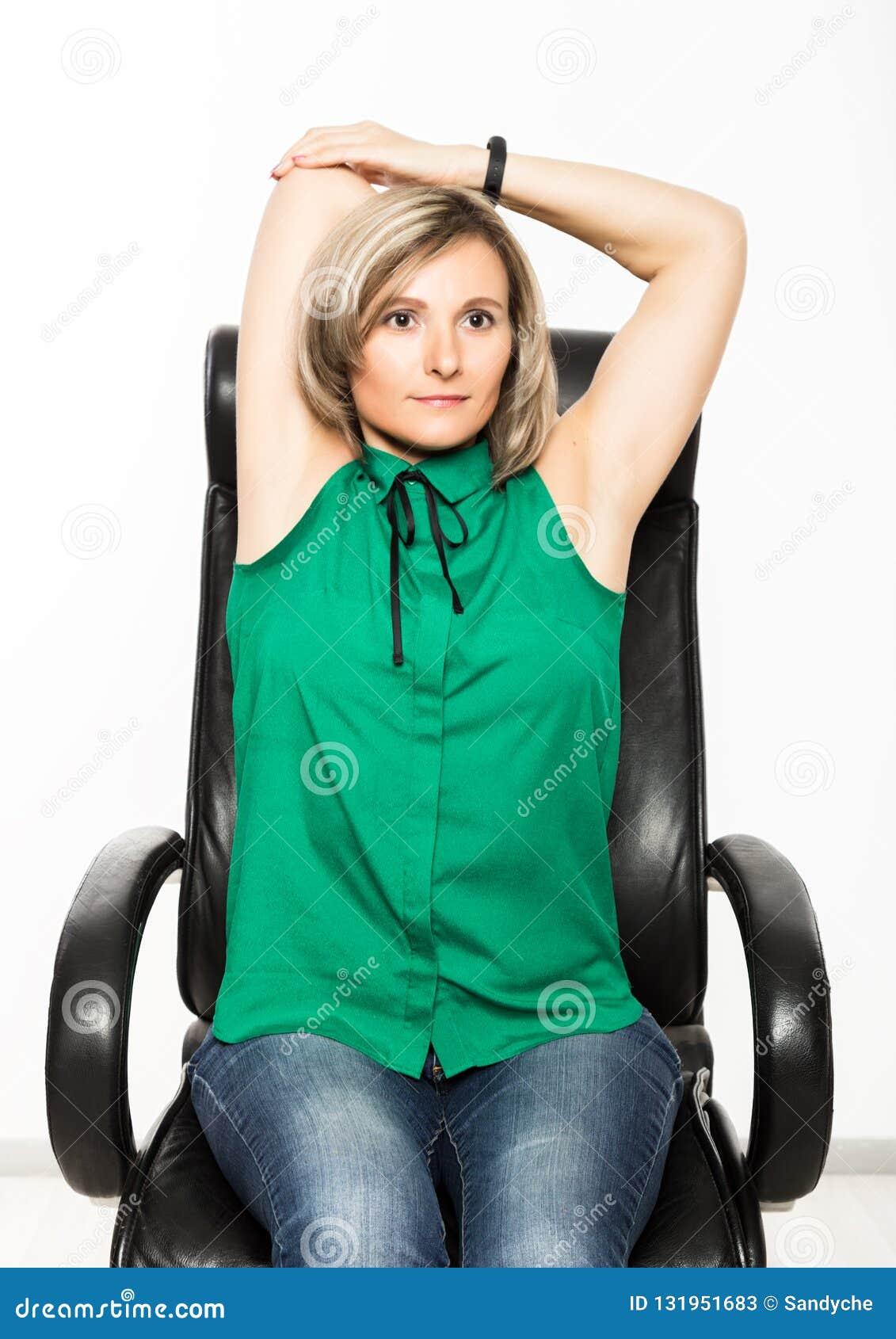 Ung affärskvinna som sitter på stol som gör konditionövning på arbetsplatsen