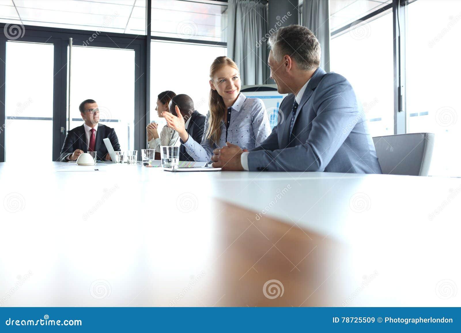 Ung affärskvinna som talar med den manliga kollegan i mötesrum