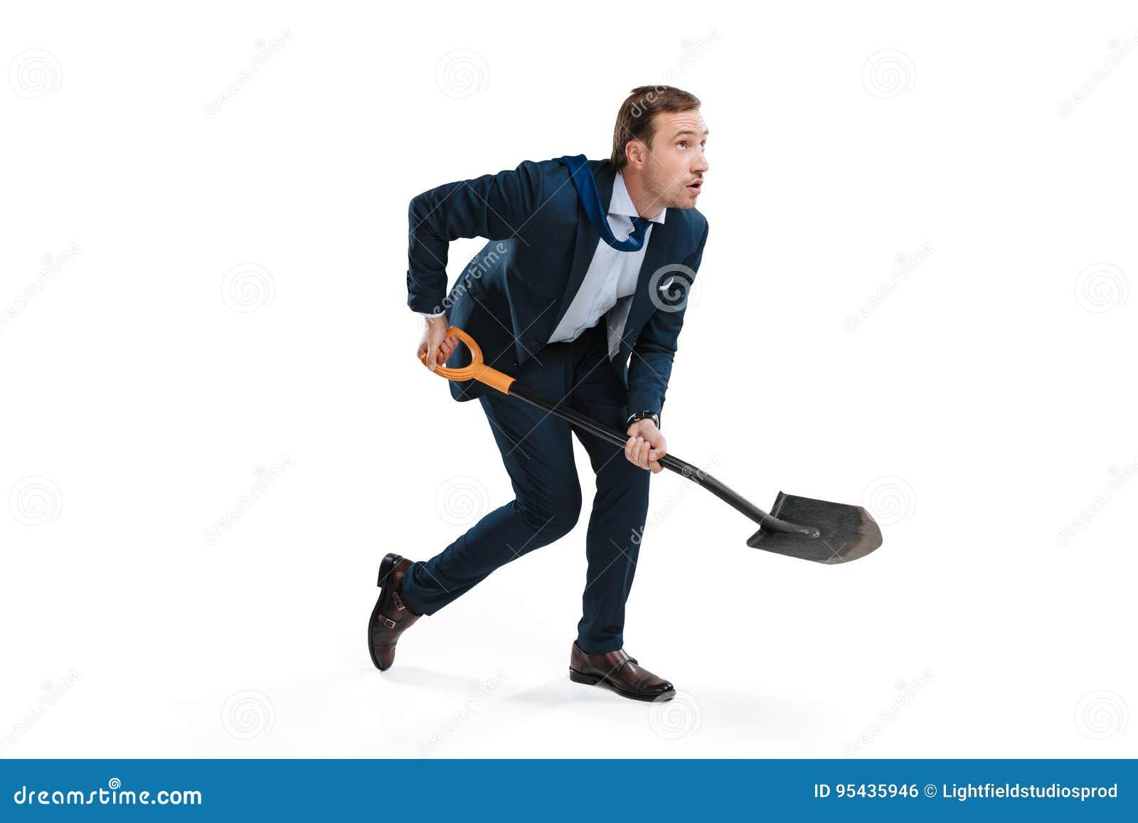 Ung affärsman i formella kläder som gräver med skyffeln och bort ser