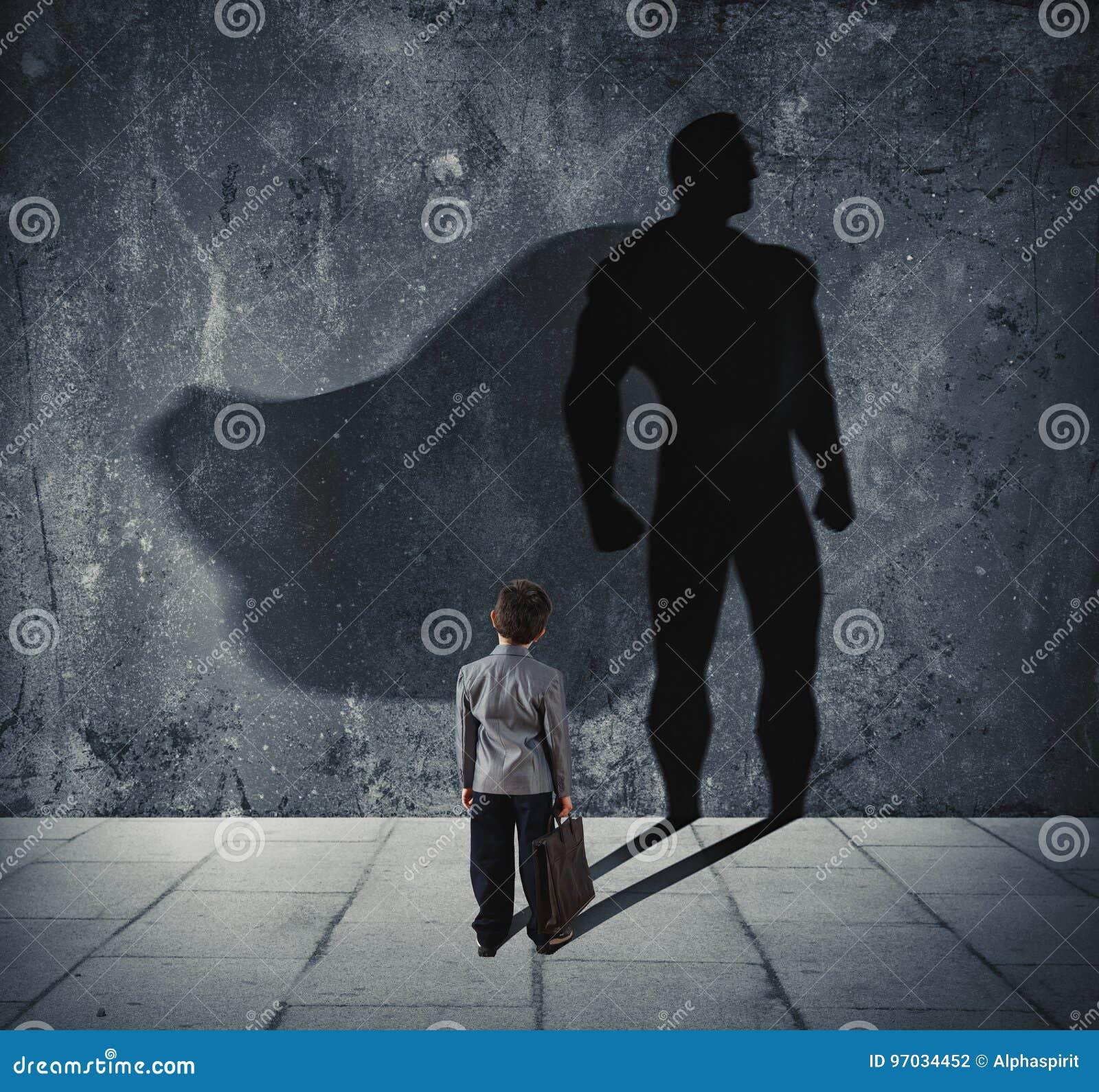 Ung affärsman med hans skugga av den toppna hjälten på väggen Begrepp av den kraftiga lilla mannen