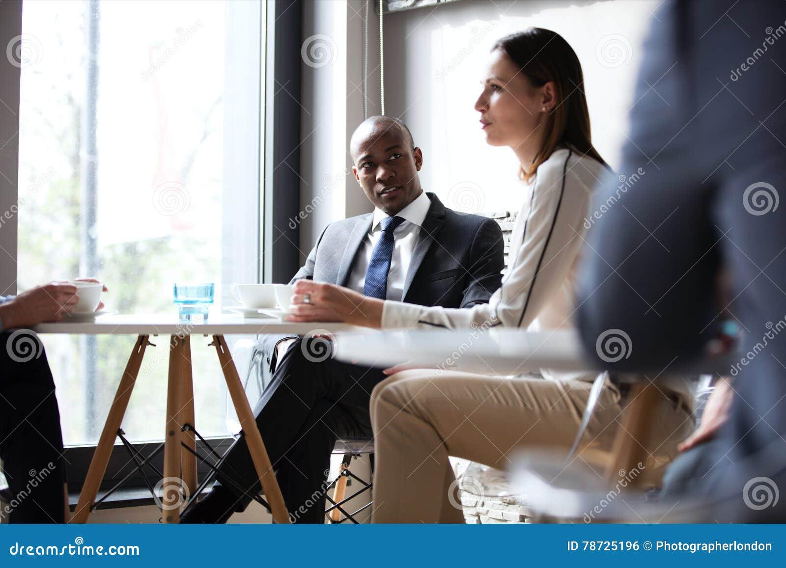 Ung affärsman med kollegor som har kaffe i regeringsställning