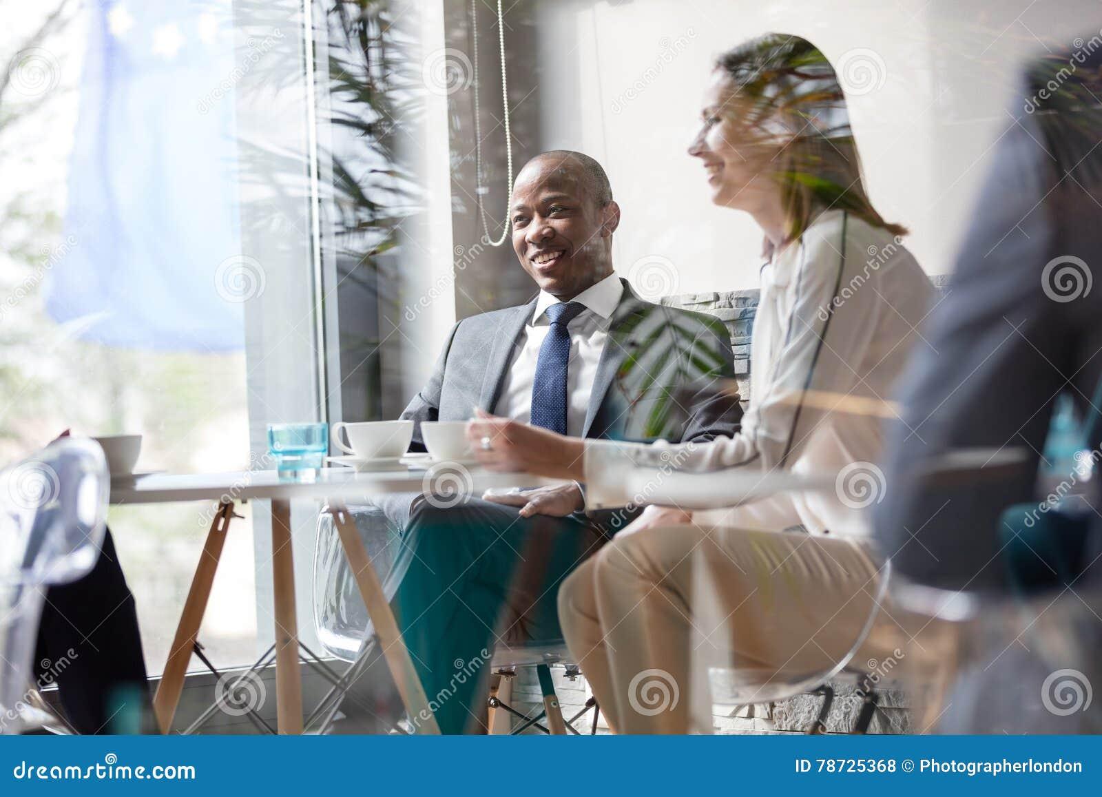 Ung affärsman med kollegor som har kaffe på tabellen i regeringsställning