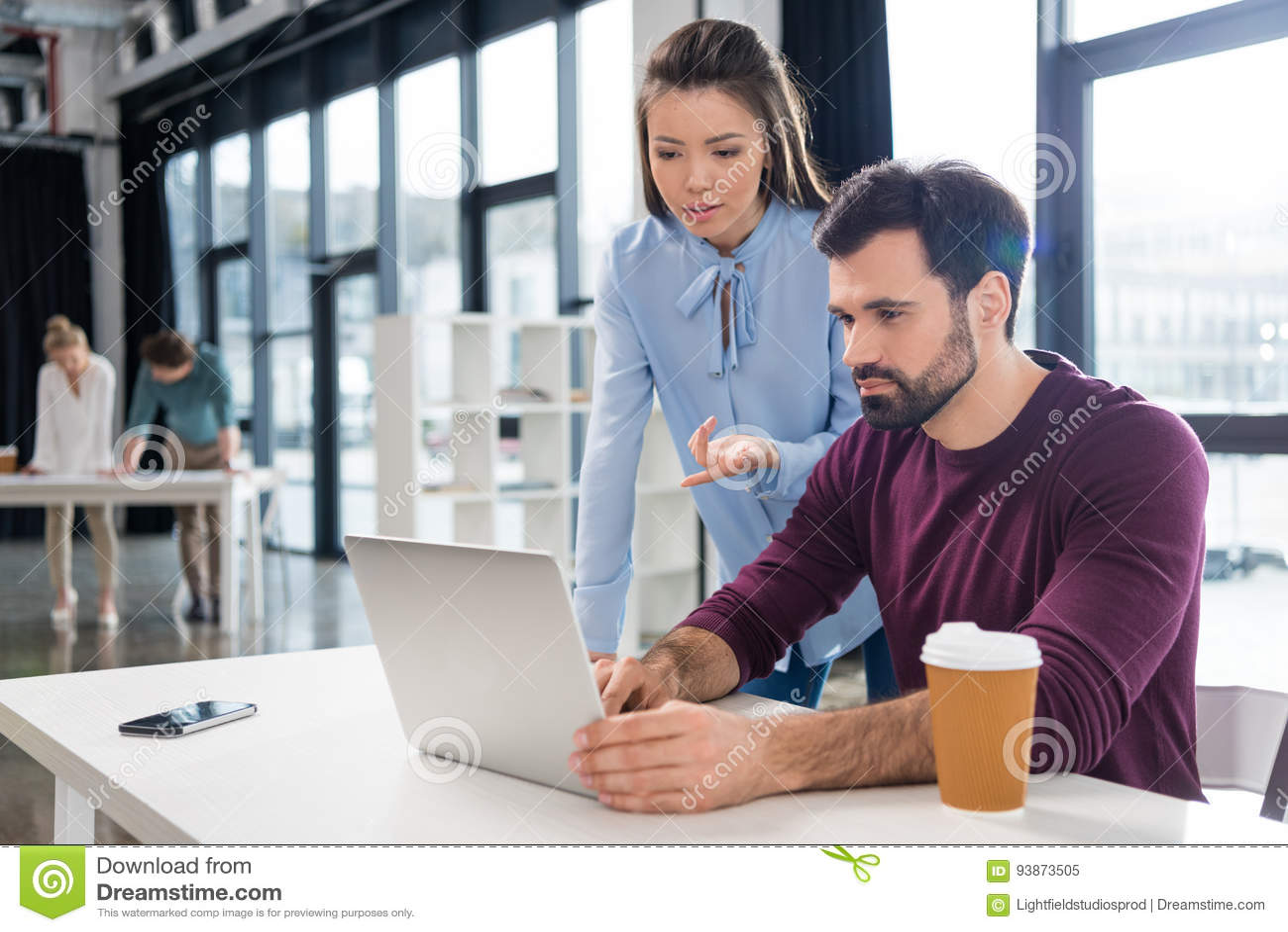 Ung affärsman och affärskvinna som arbetar med bärbara datorn i små och medelstora företagkontor