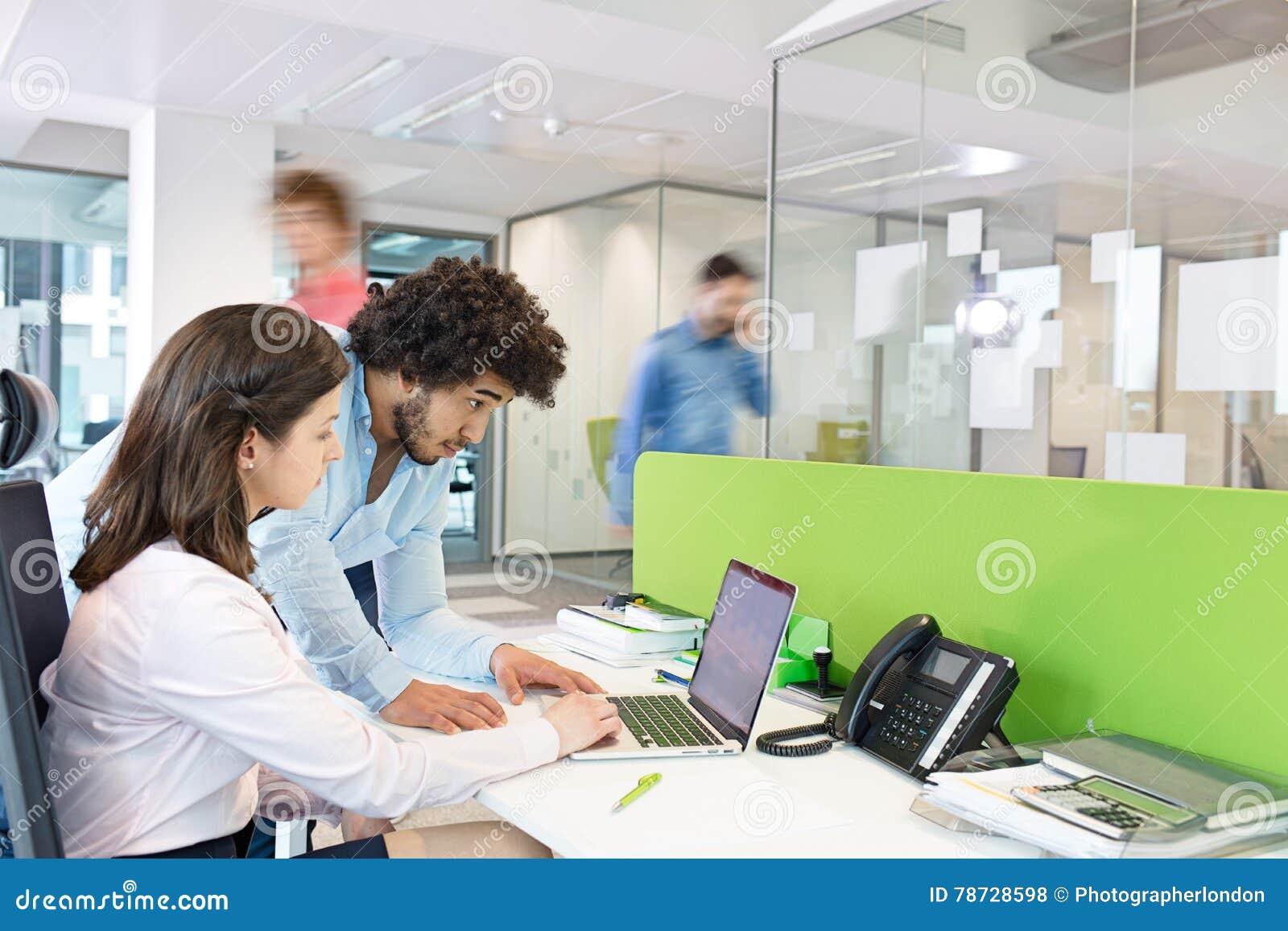 Ung affärsman och affärskvinna som i regeringsställning använder bärbara datorn på skrivbordet