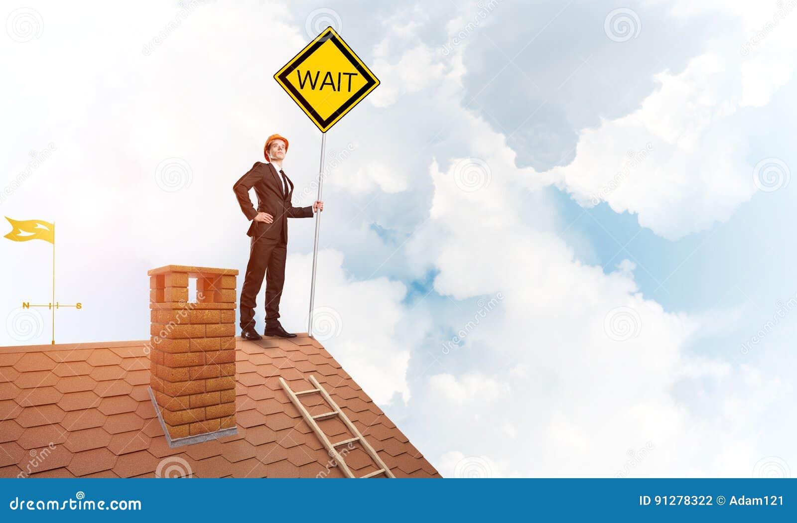 Ung affärsman på skylt för guling för innehav för hustegelstentak Blandat massmedia