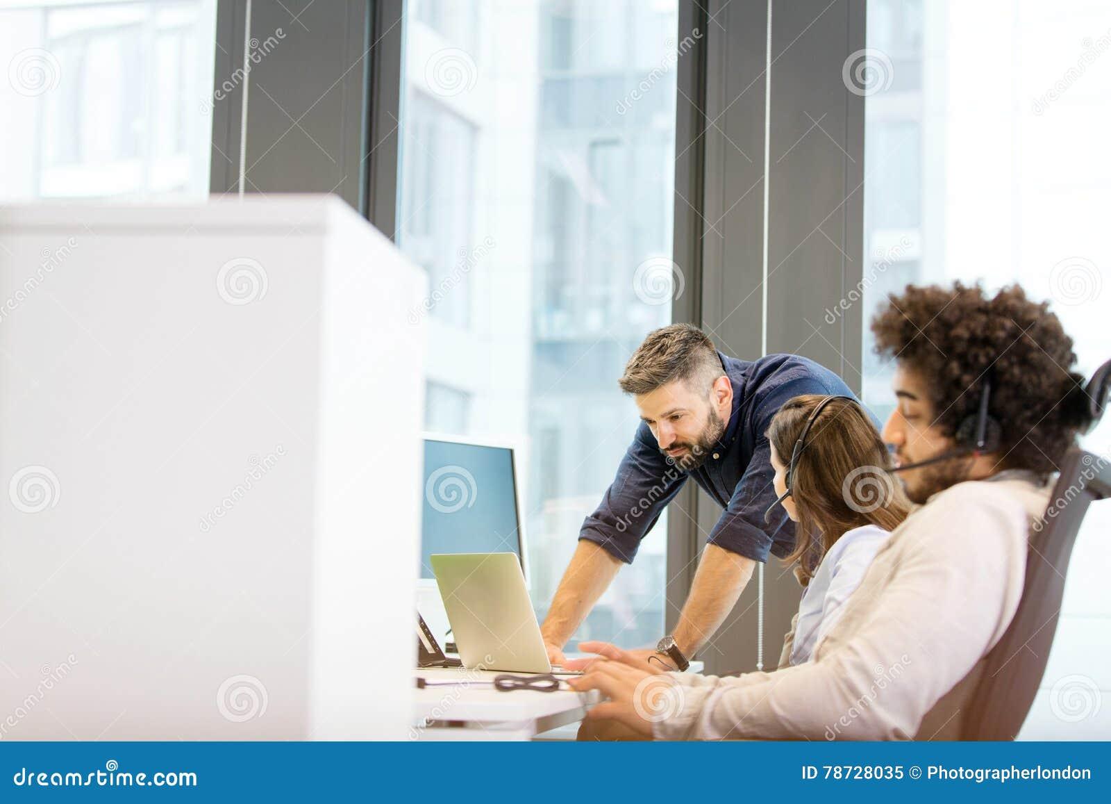 Ung affärsman som använder hörlurar med mikrofon med kollegor som diskuterar i bakgrund