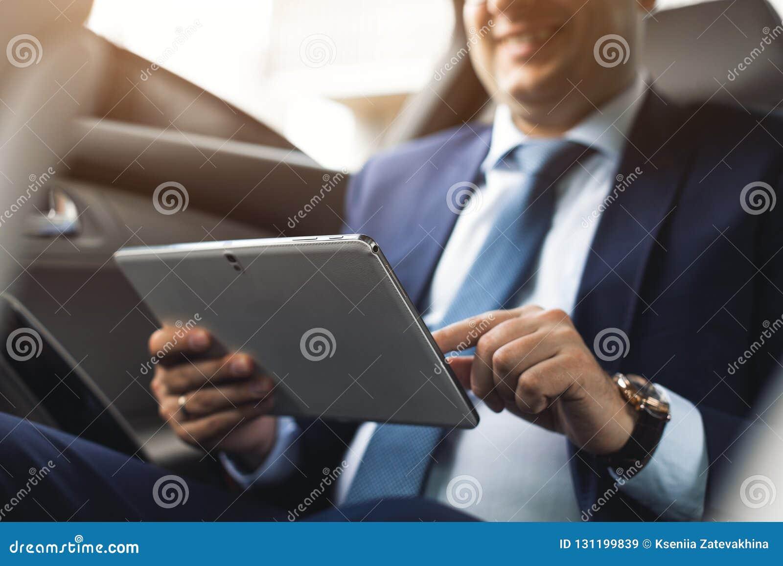 Ung affärsman som använder minnestavlaPC, medan sitta på baksätet av en bil Caucasian manlig affärsledare vid en taxi och