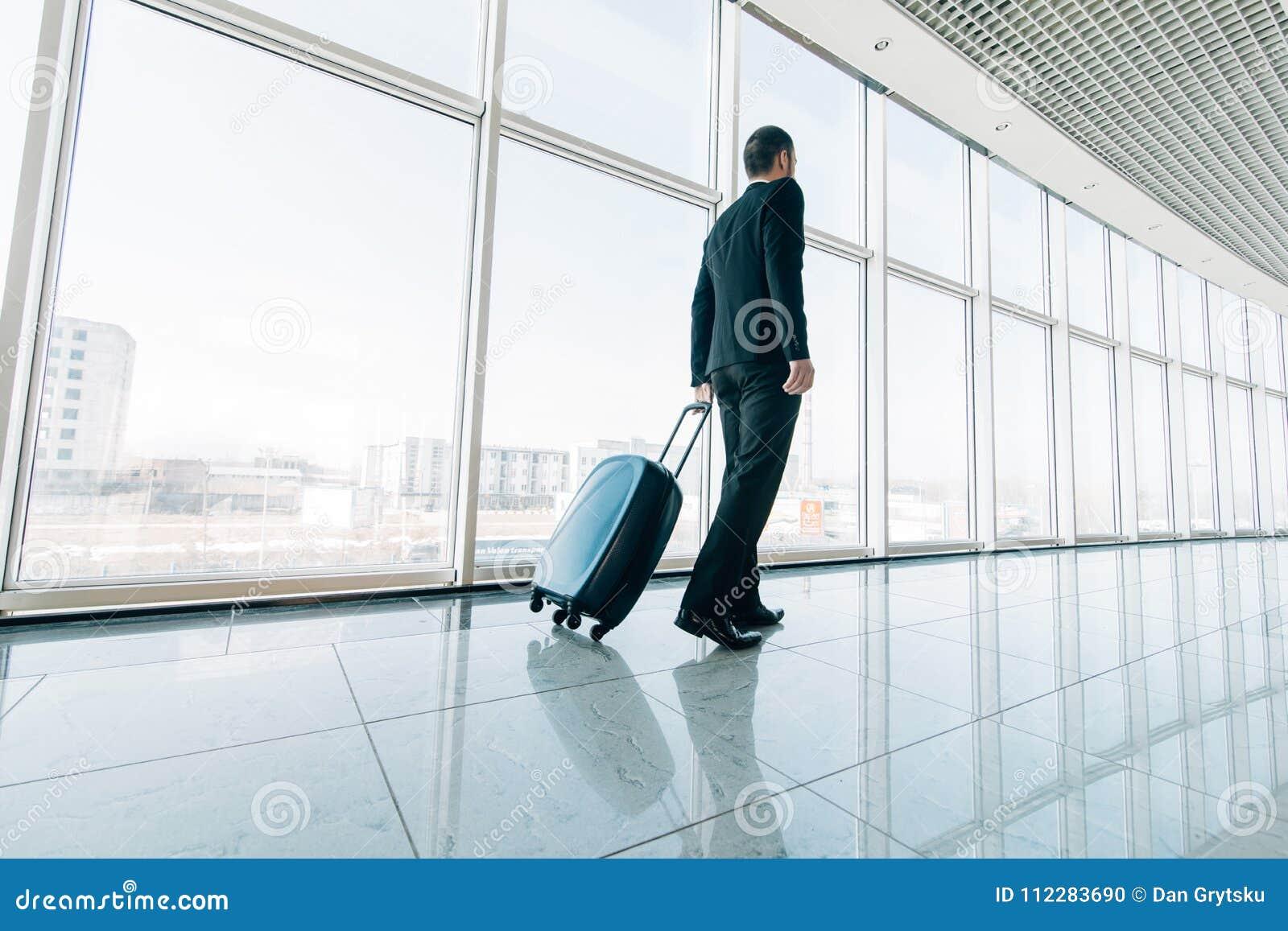 Ung affärsman som drar resväskan i modern flygplatsterminal Resande grabb- eller affärsmanbegrepp affären rymmer tur för manstand
