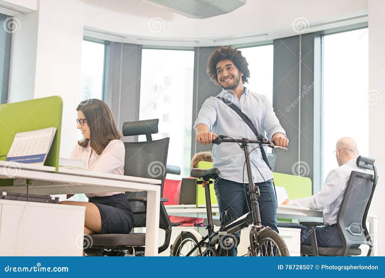 Ung affärsman som går med cykeln medan kollegor som i regeringsställning arbetar