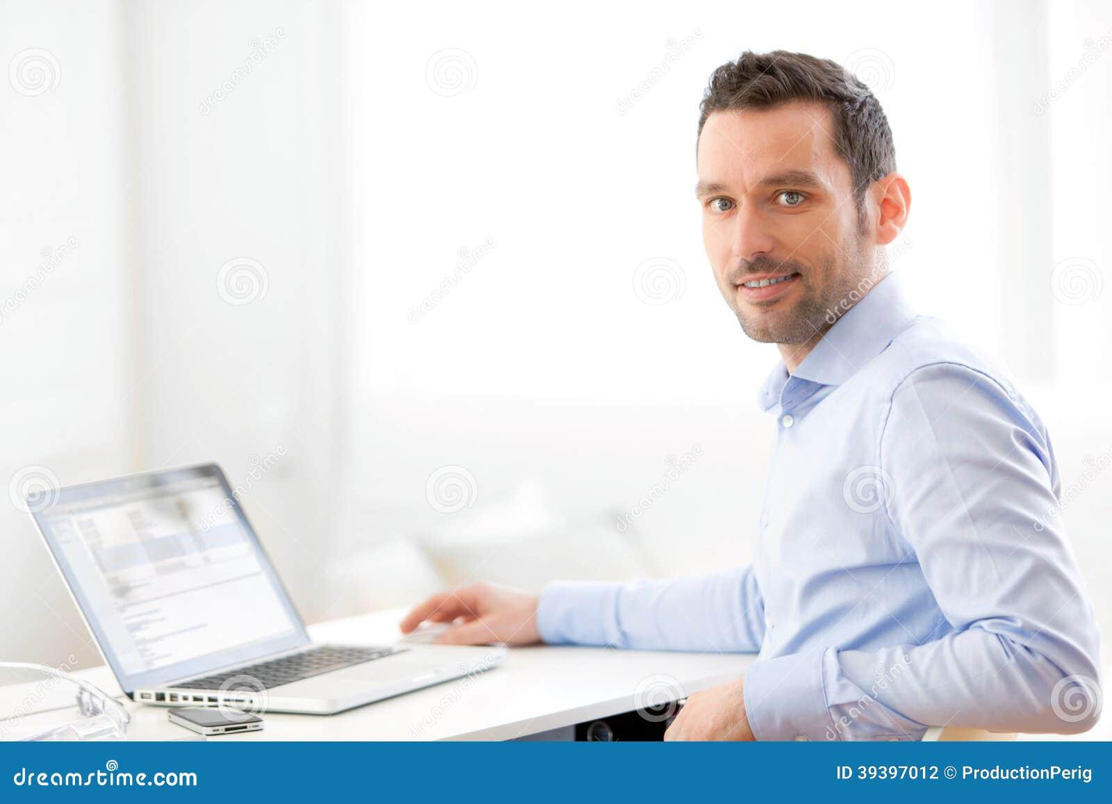 Ung affärsman som hemma arbetar på hans bärbar dator