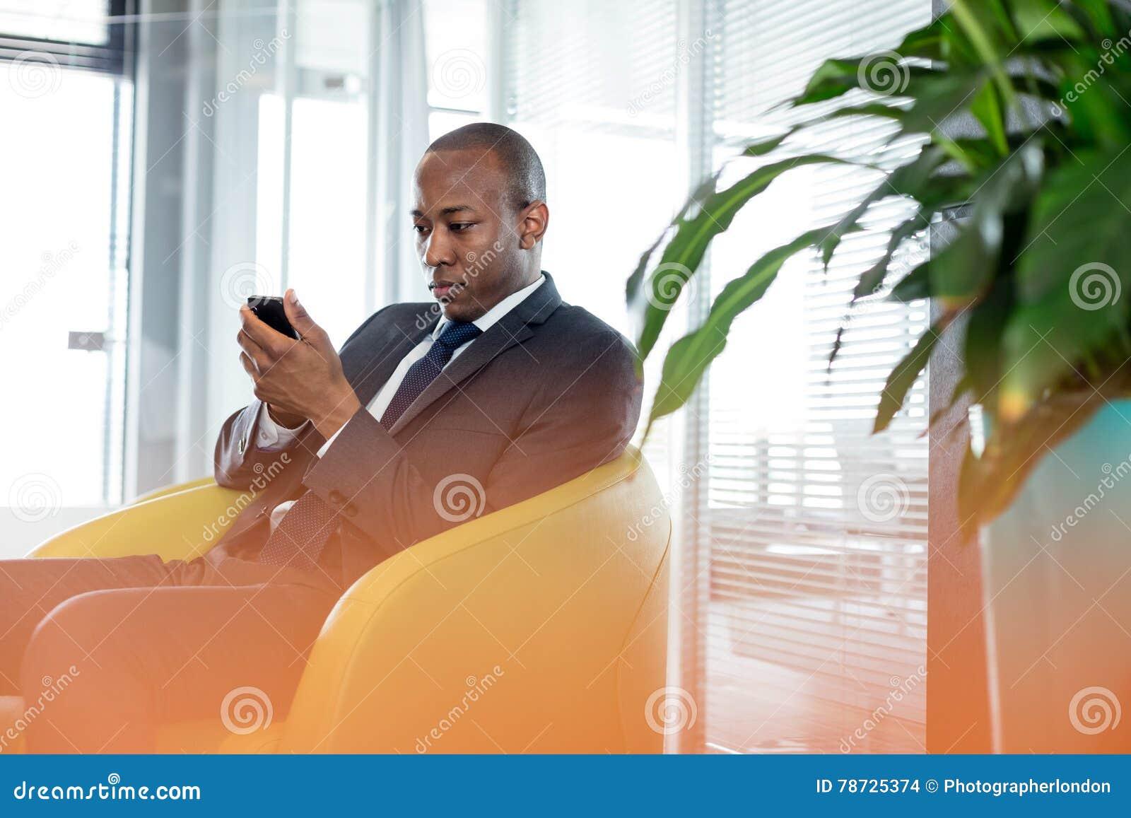 Ung affärsman som i regeringsställning använder mobiltelefonen på stol