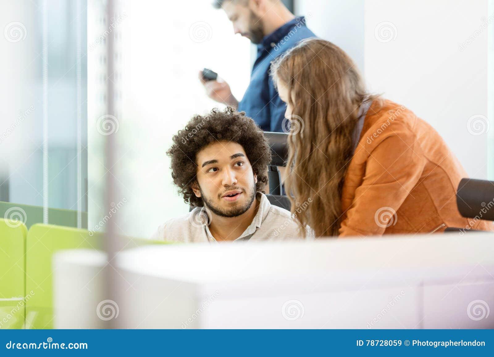 Ung affärsman som i regeringsställning talar med den kvinnliga kollegan