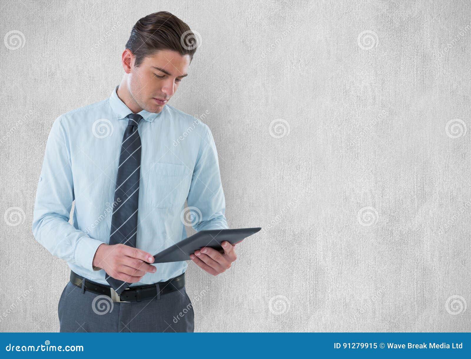 Ung affärsman som rymmer den digitala minnestavlan mot väggen