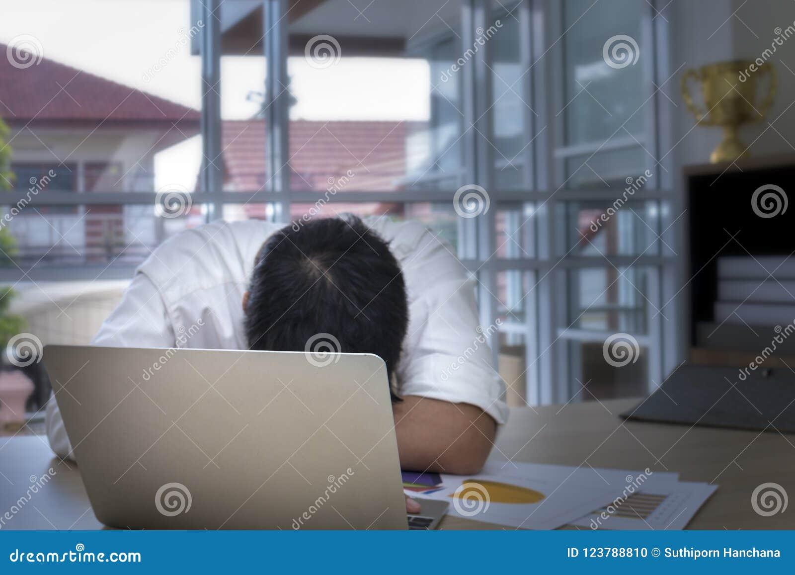 Ung affärsman som sover och överansträngas nära bärbara datorn på kontoret
