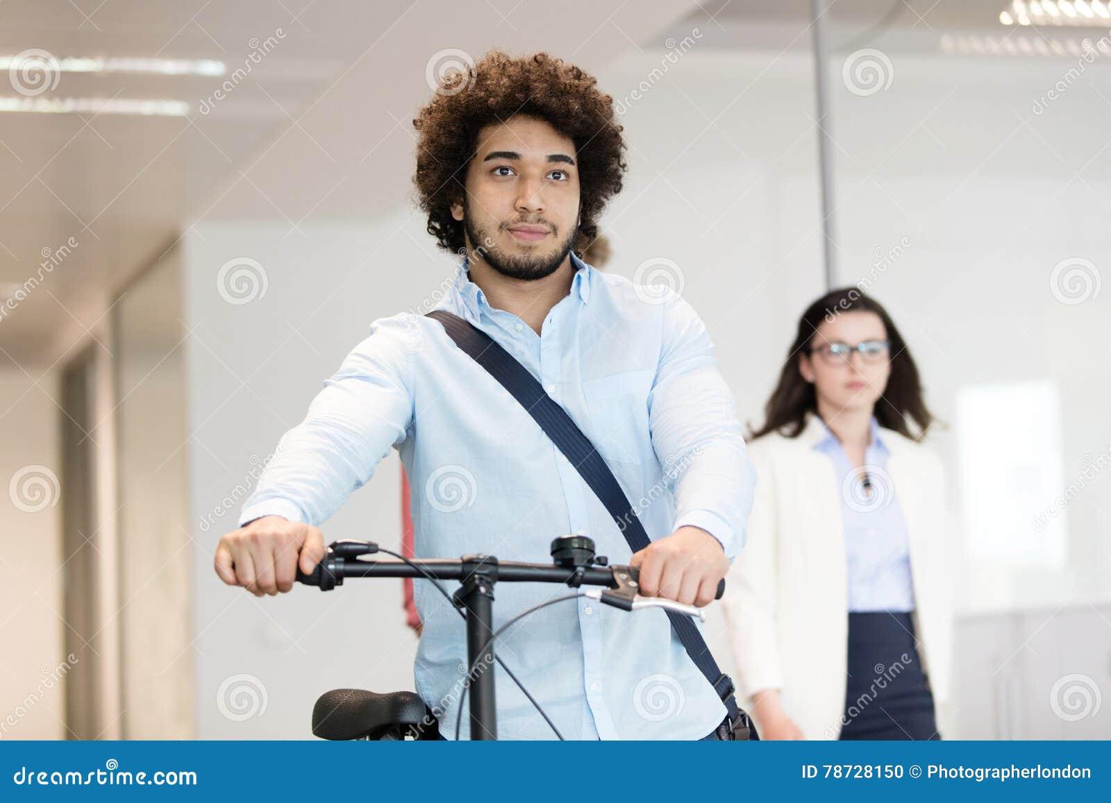 Ung affärsmaninnehavcykel med den kvinnliga kollegan i bakgrund på kontoret