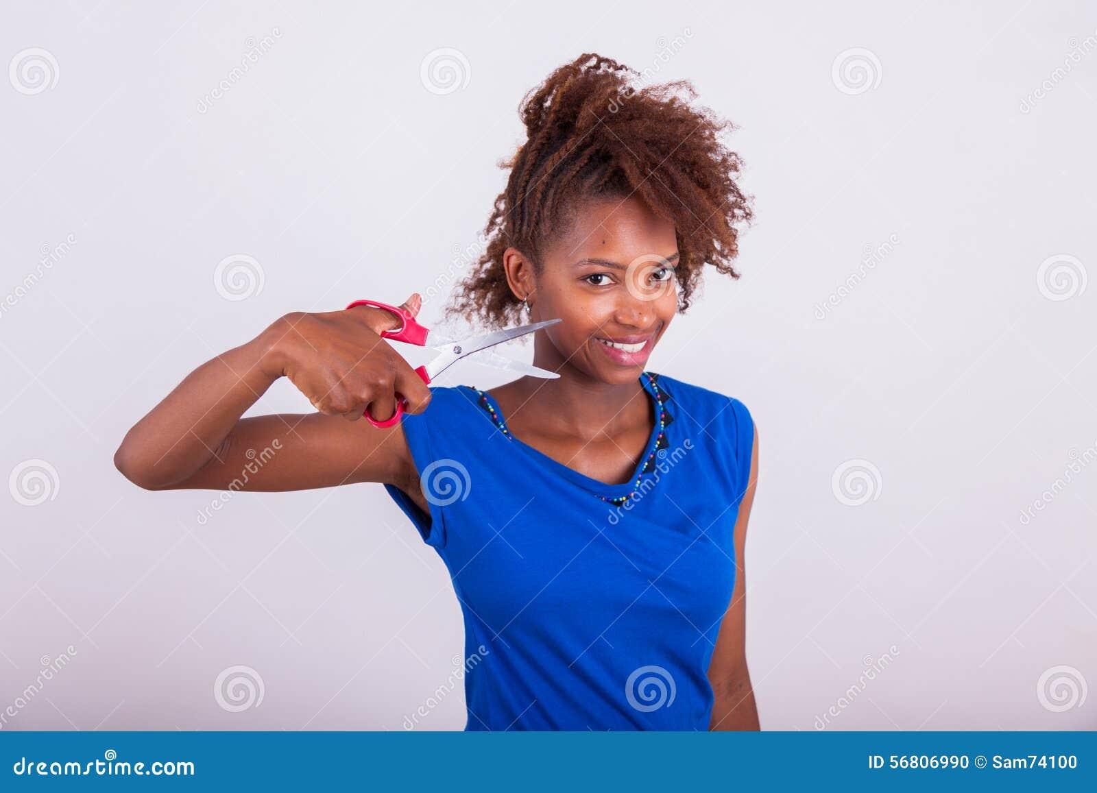 Ung afrikansk amerikankvinna som klipper hennes burriga afro hår med s