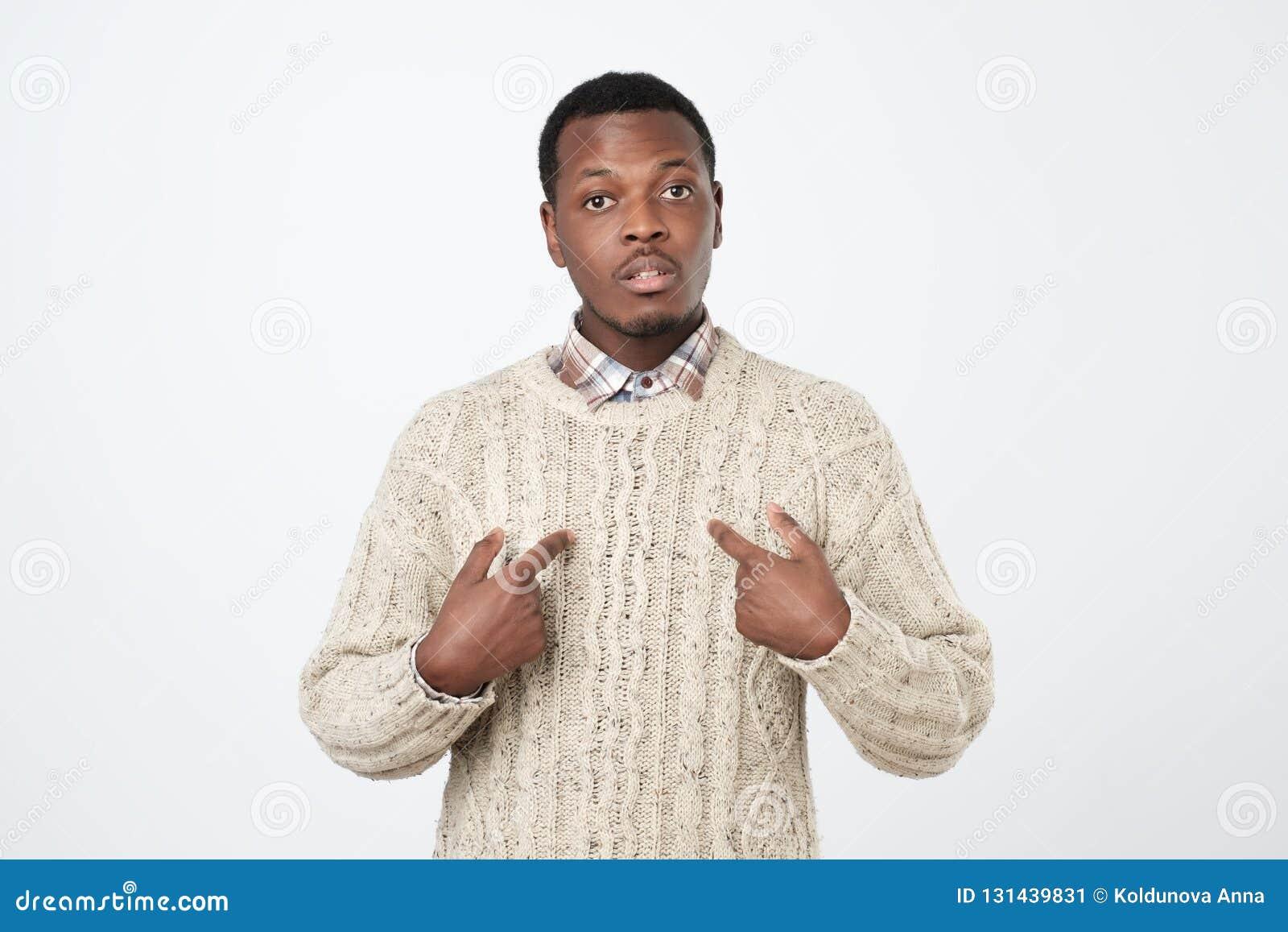Ung afrikansk man som pekar på honom och att göra ursäkter eller försvar muntligt, som har förvirrat och förbryllas Uttryck för m
