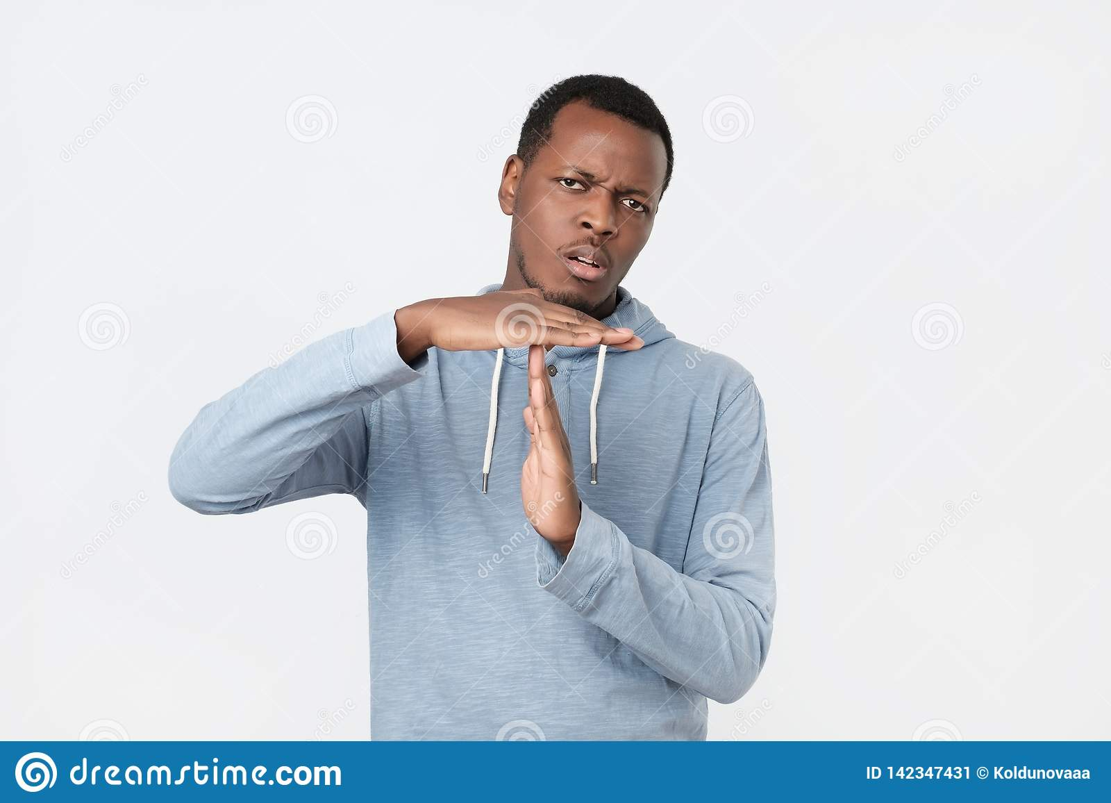 Ung afrikansk man som ut visar handgest för tid