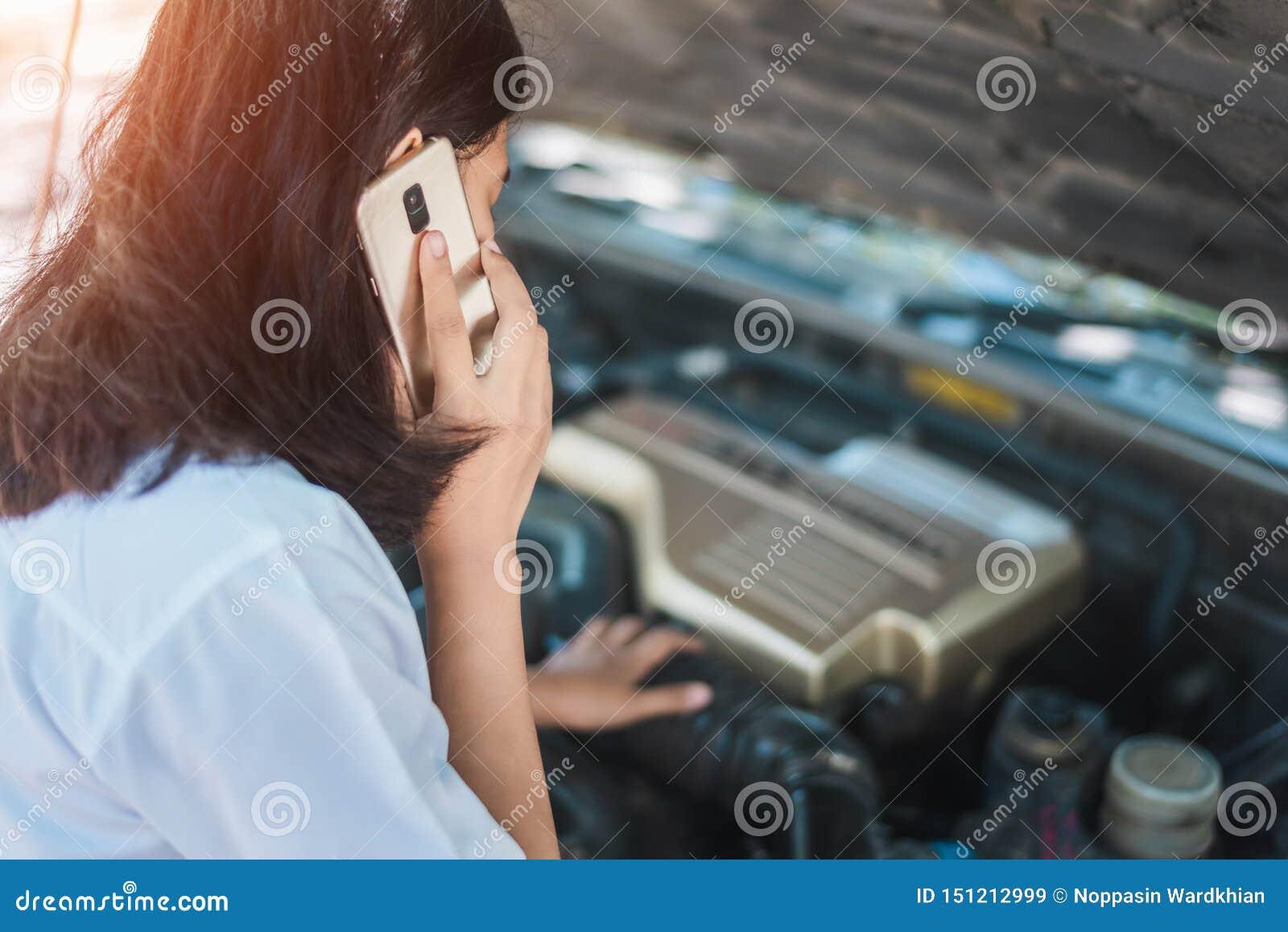 Ung asia kvinna som framme sitter av hennes bil, f?rs?k till att kalla f?r hj?lp med hennes brutna down f?r bil