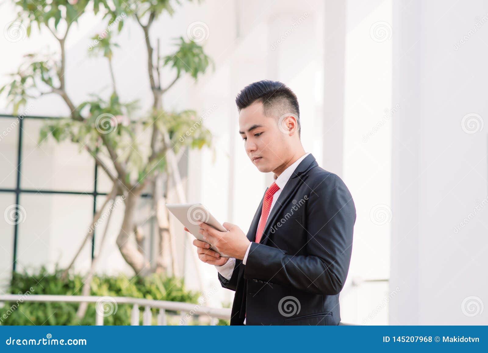 Ung asiatisk aff?rsman som arbetar p? minnestavlan, livsstil av den moderna mannen f?r att meddela, meddelande- eller bruksteknol