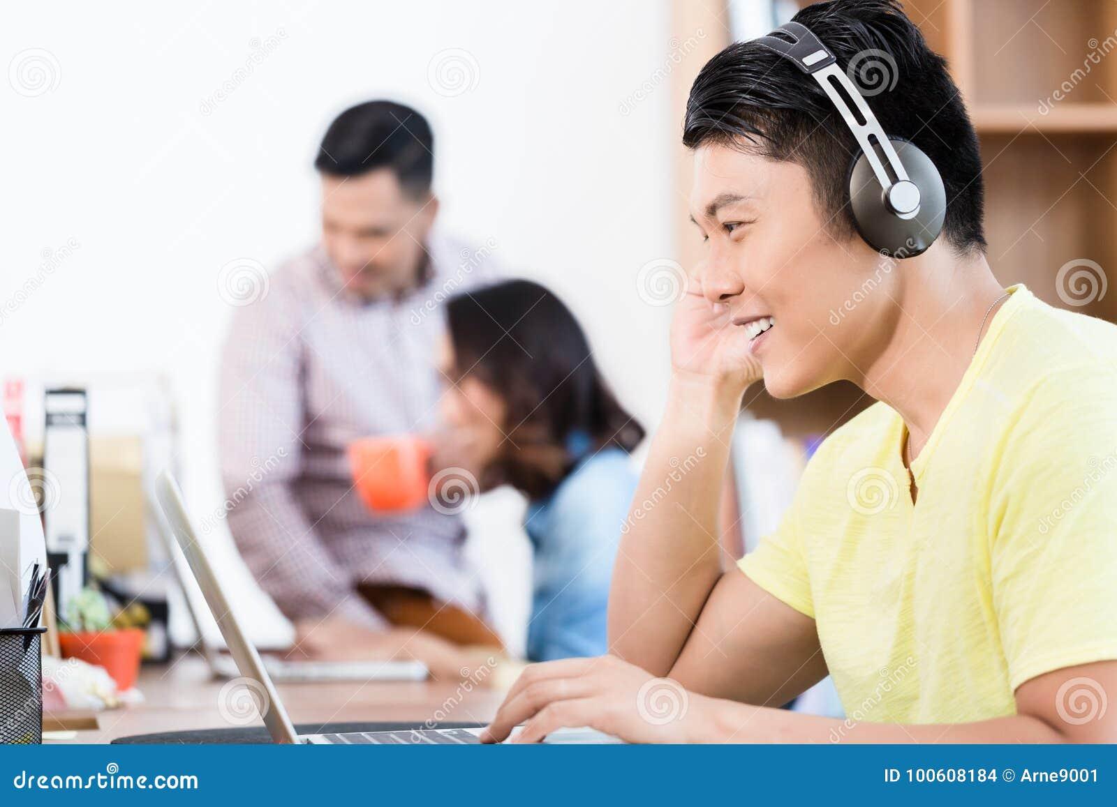 Ung asiatisk anställd som in håller ögonen på en video presentation på bärbara datorn