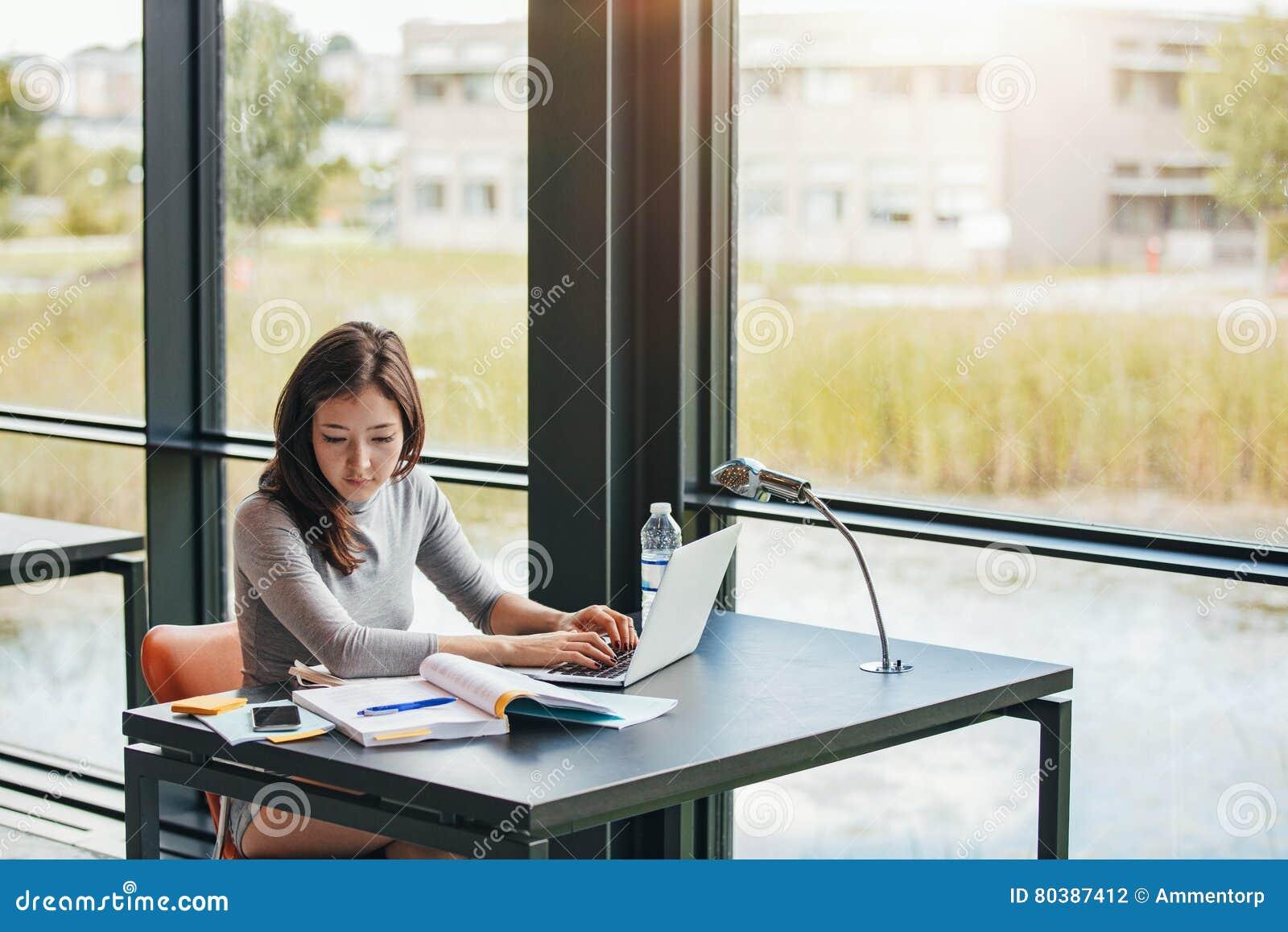 Ung asiatisk kvinna i arkivet som gör uppgifter