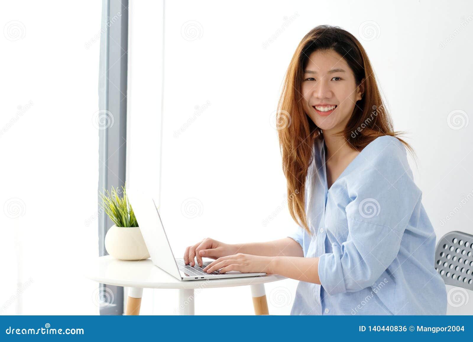 Ung asiatisk kvinna i tillfällig stil genom att använda bakgrund, folk och teknologi för kontor för bärbar datordator som hemmast