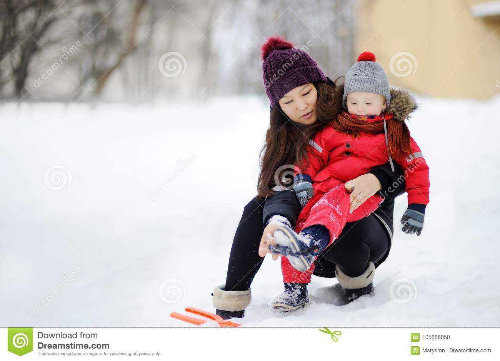 Ung asiatisk kvinna som hjälper den caucasian litet barnpojken med hans vinterkläder