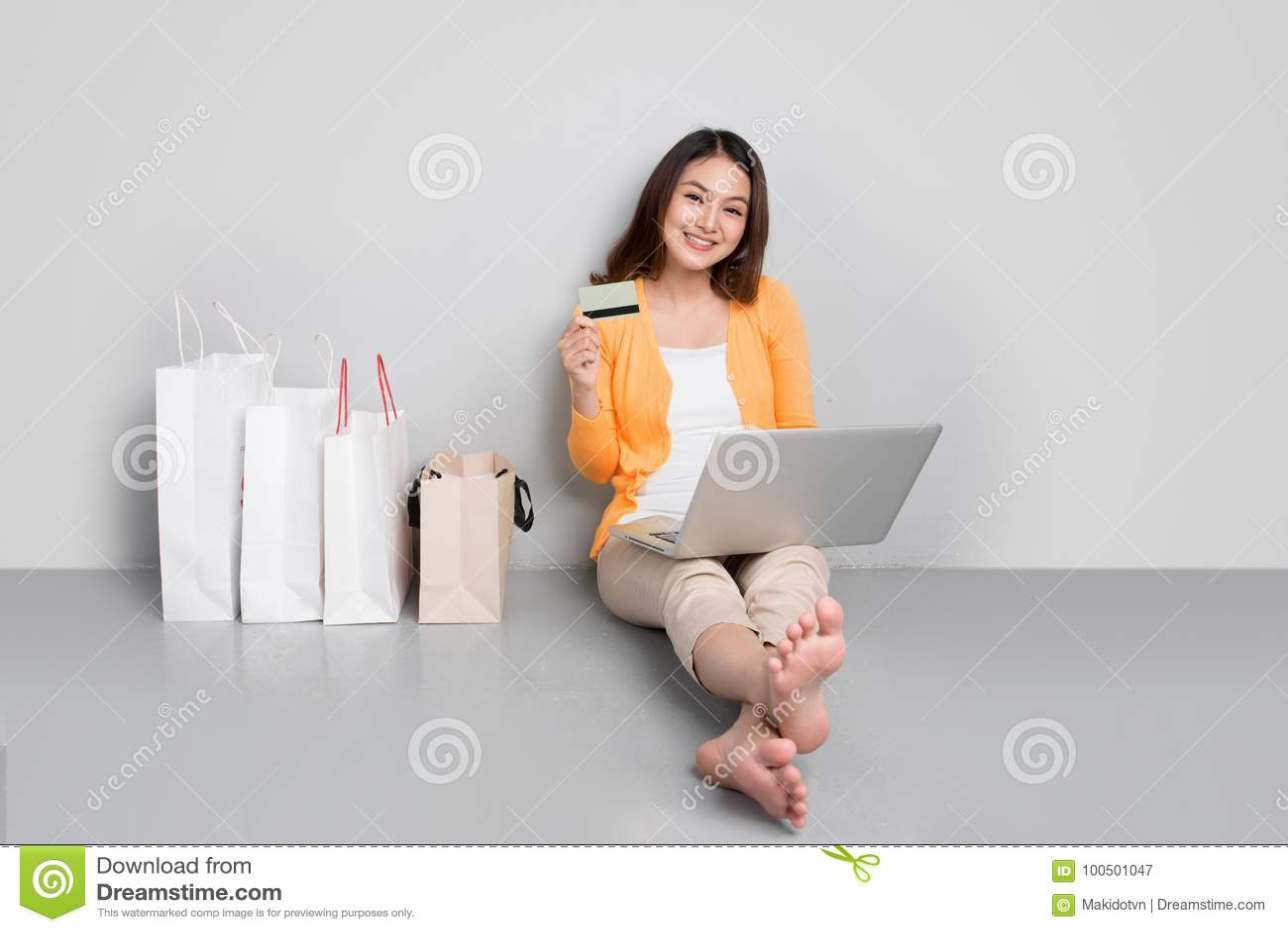 Ung asiatisk kvinna som shoppar online-hemmastatt sammanträde förutom rad av