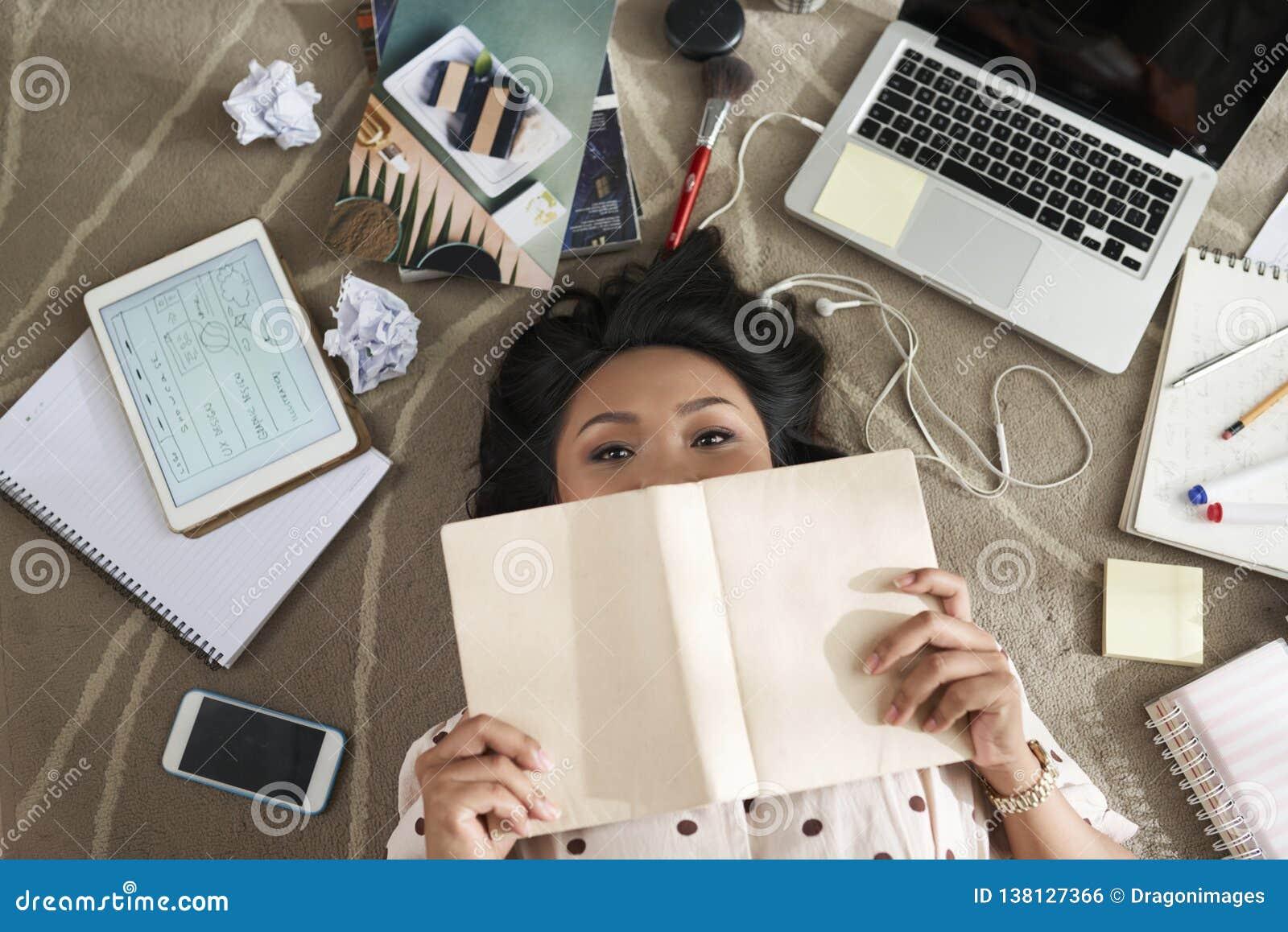 Ung asiatisk kvinnlig högskolaflicka i avläggande av examenkappan som isoleras på vit bakgrund