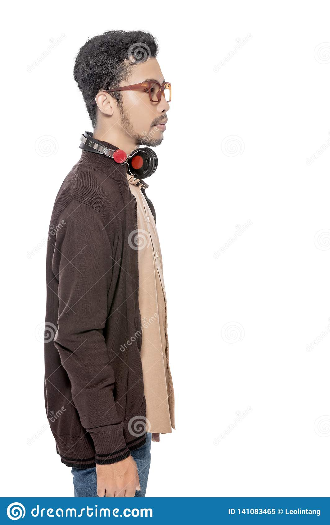 Ung asiatisk man i brunt omslagsanseende med hörlurar på hans hals