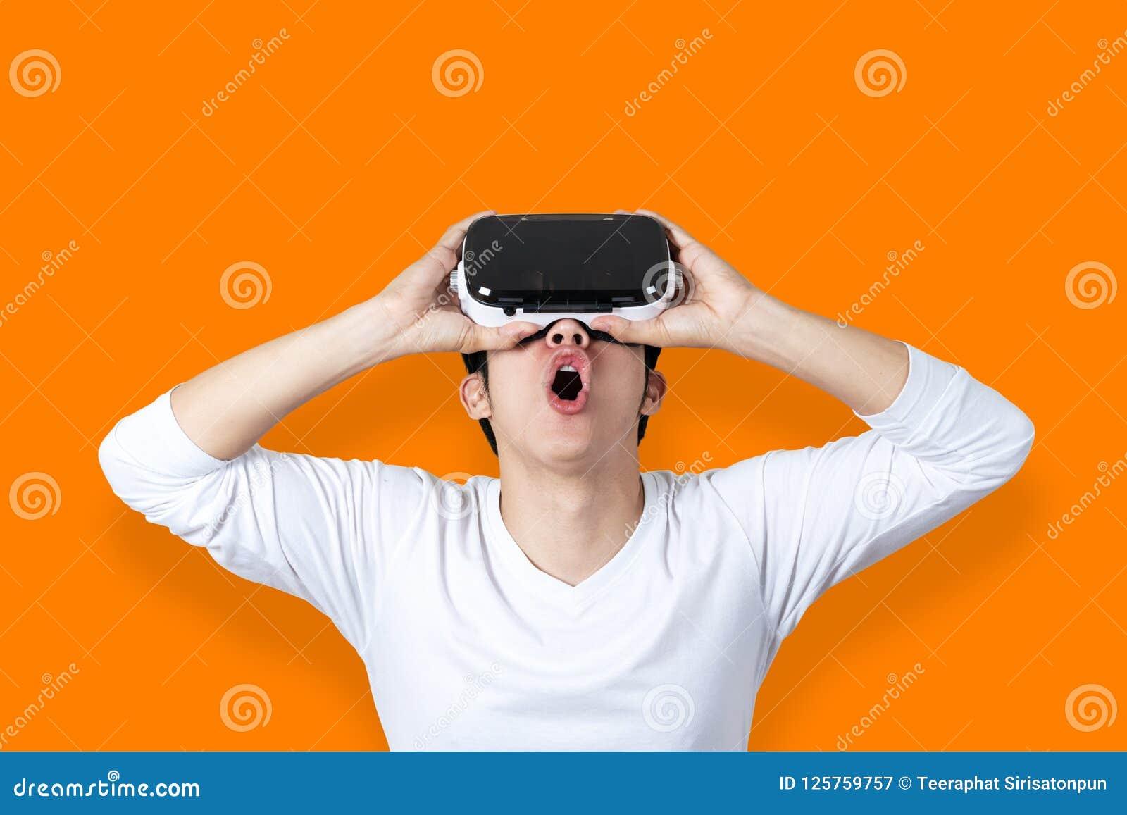 Ung asiatisk man som förbluffas av virtuell verklighet