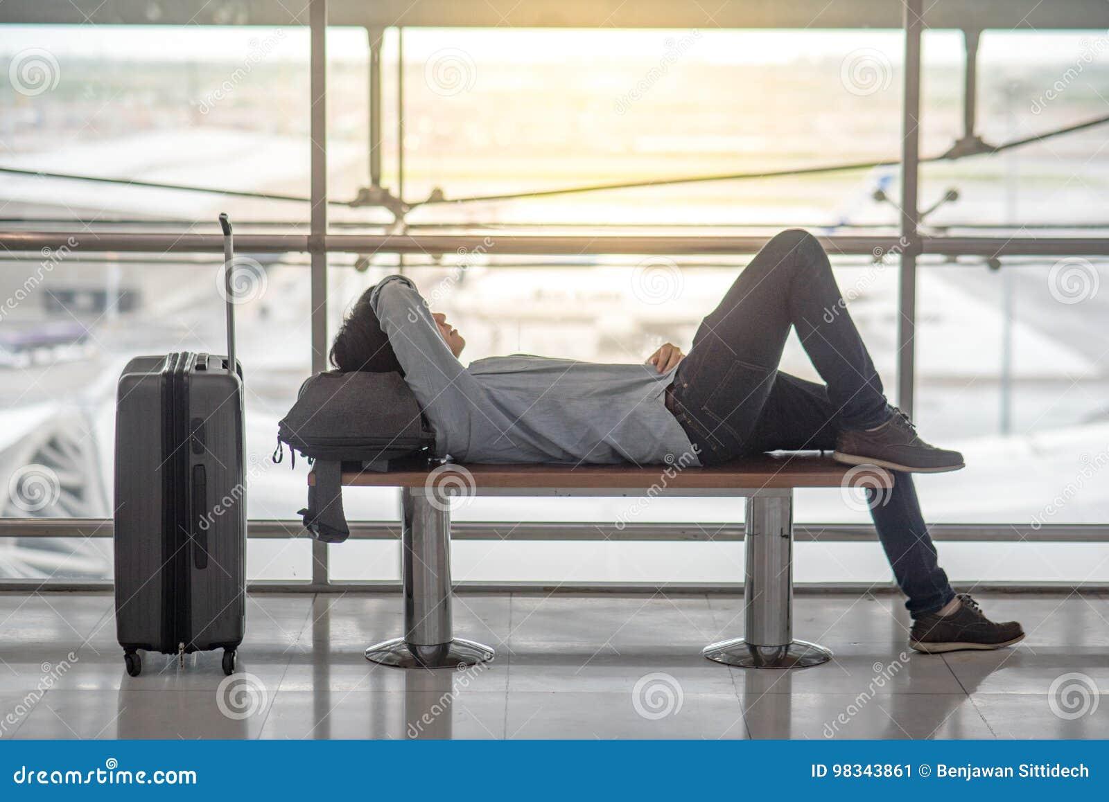 Ung asiatisk man som ligger på bänk i flygplatsterminal
